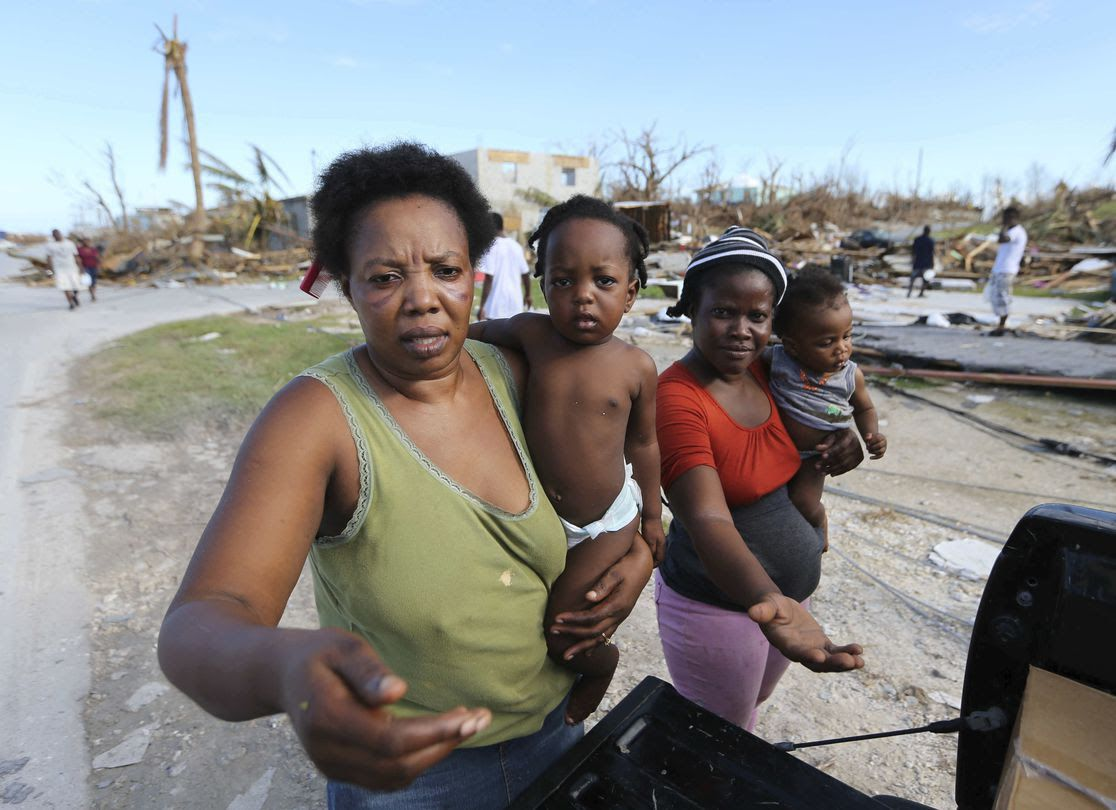 Residents of an area destroyed by Hurricane Dorian ask for food and water from rescue volunteers in Bahamas.