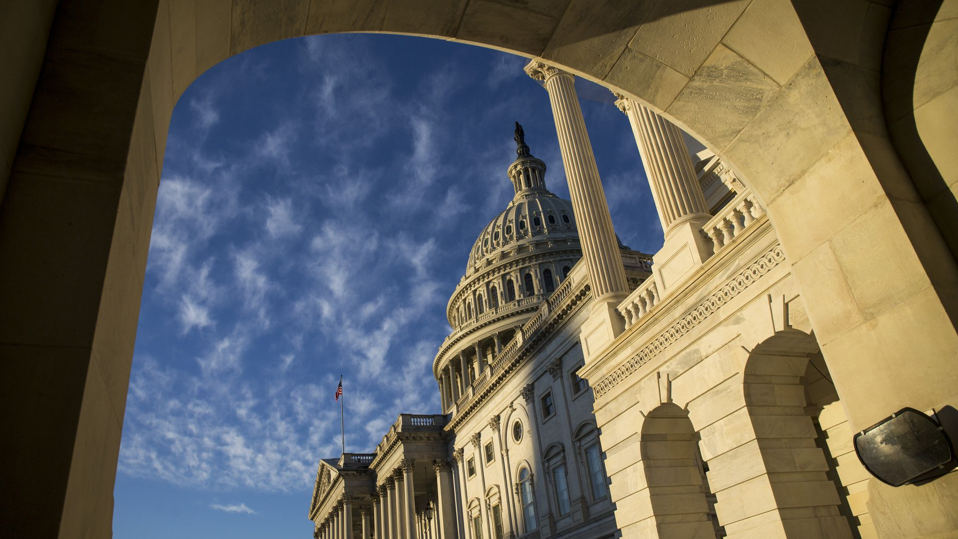 The exterior of the Capitol dome pictured through an archway