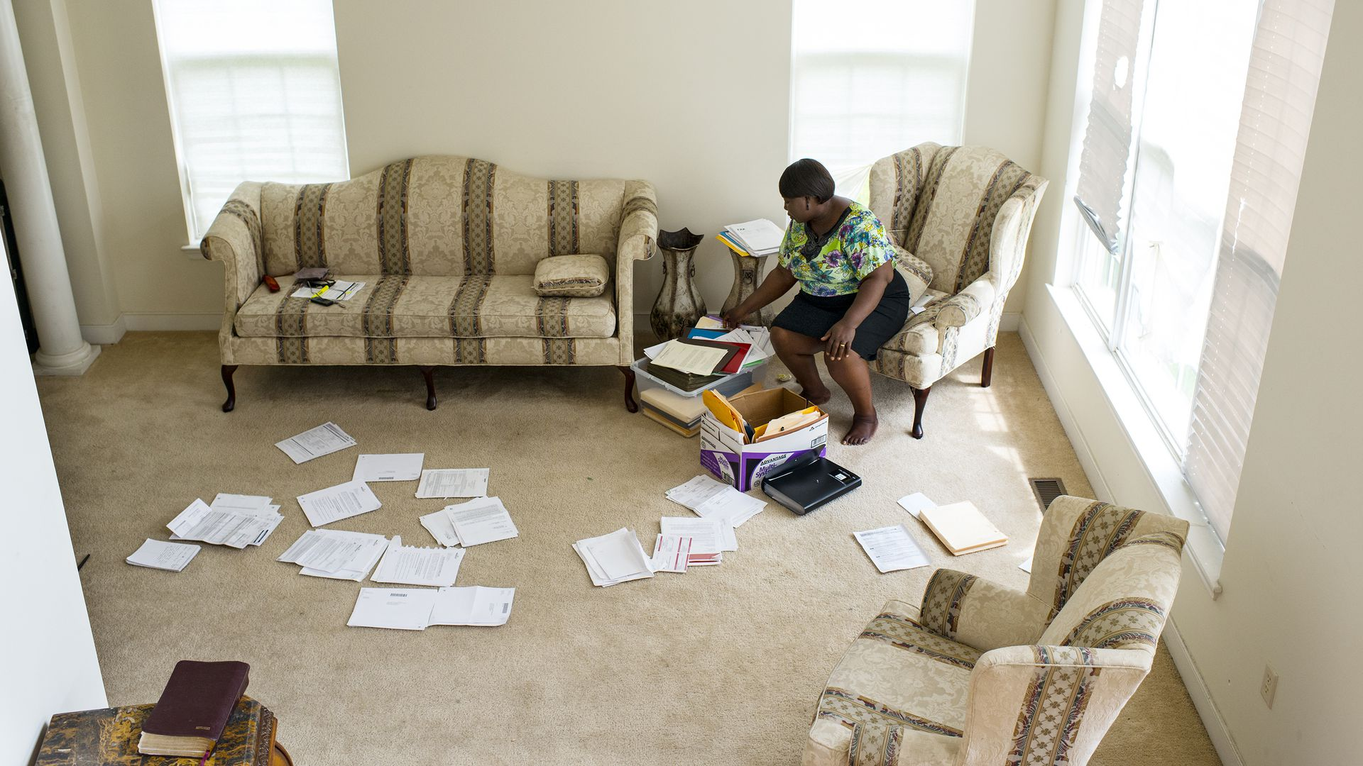 A woman sits in a room with papers scattered on the floor.