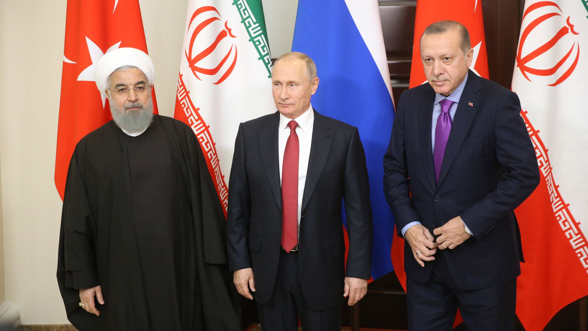 Rouhani, Putin, and Erdogan standing in front of national flags