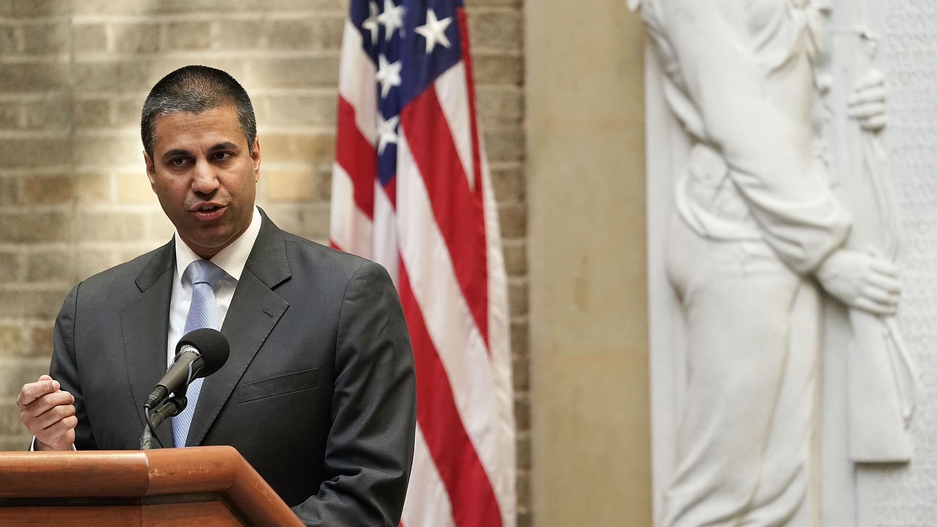 FCC Chairman Ajit Pai speaks in front of an American flag
