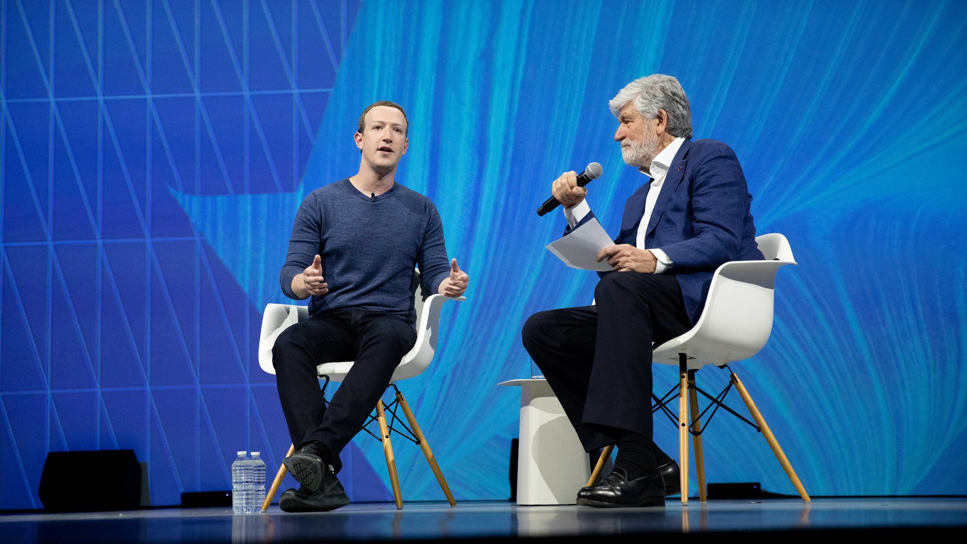 Mark Zuckerberg speaks to another man on stage at a conference