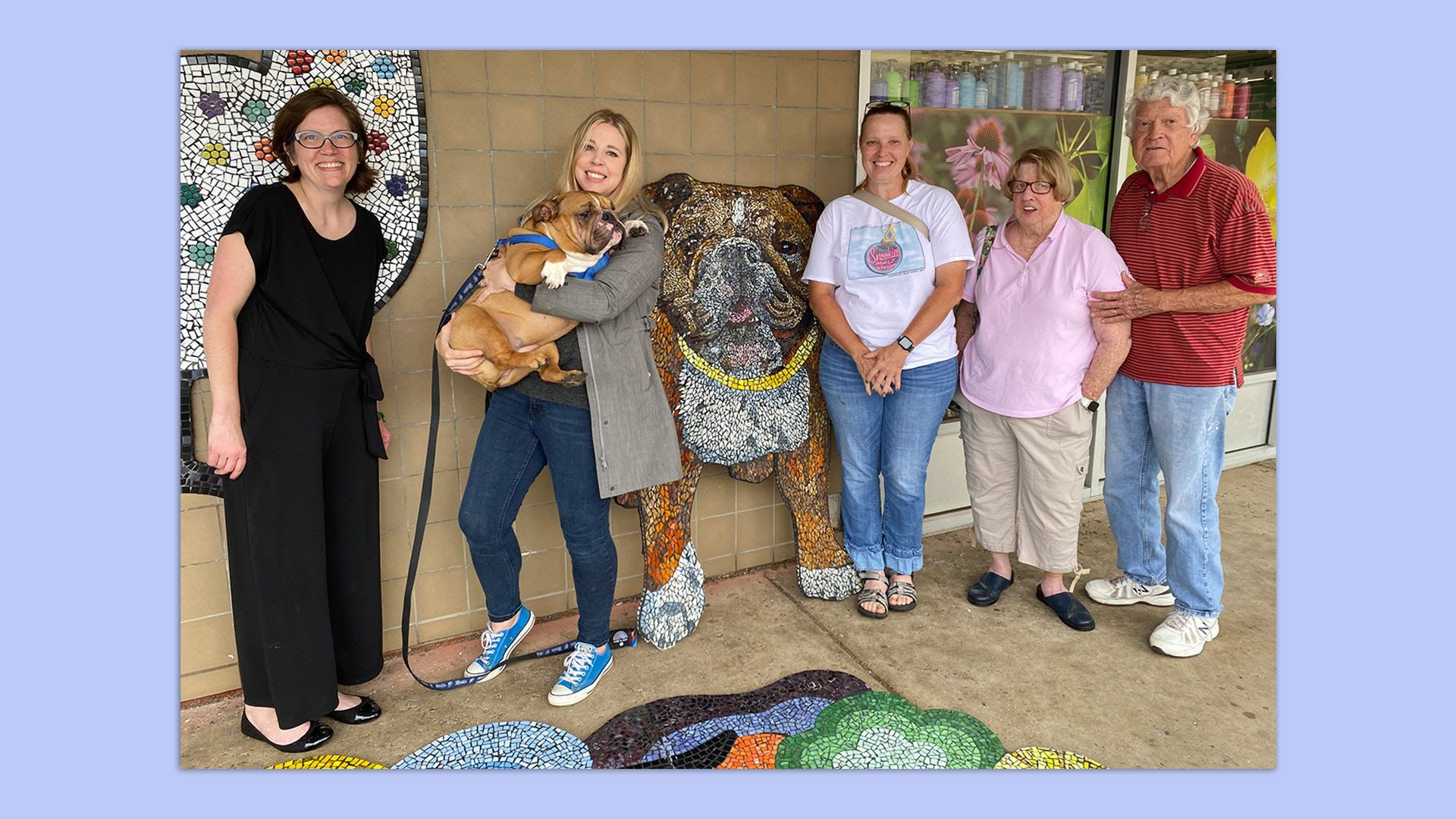 Three women (Artist Nicole James, Maggie Moller and Leslie Hunter) stand in front of James' mural of Moller's dog Frida.