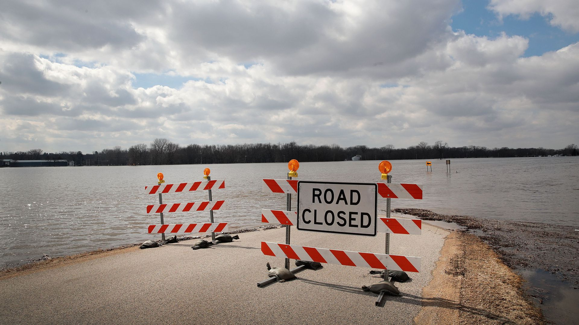 A road closed sign in front of a flooded road in the Midwest.