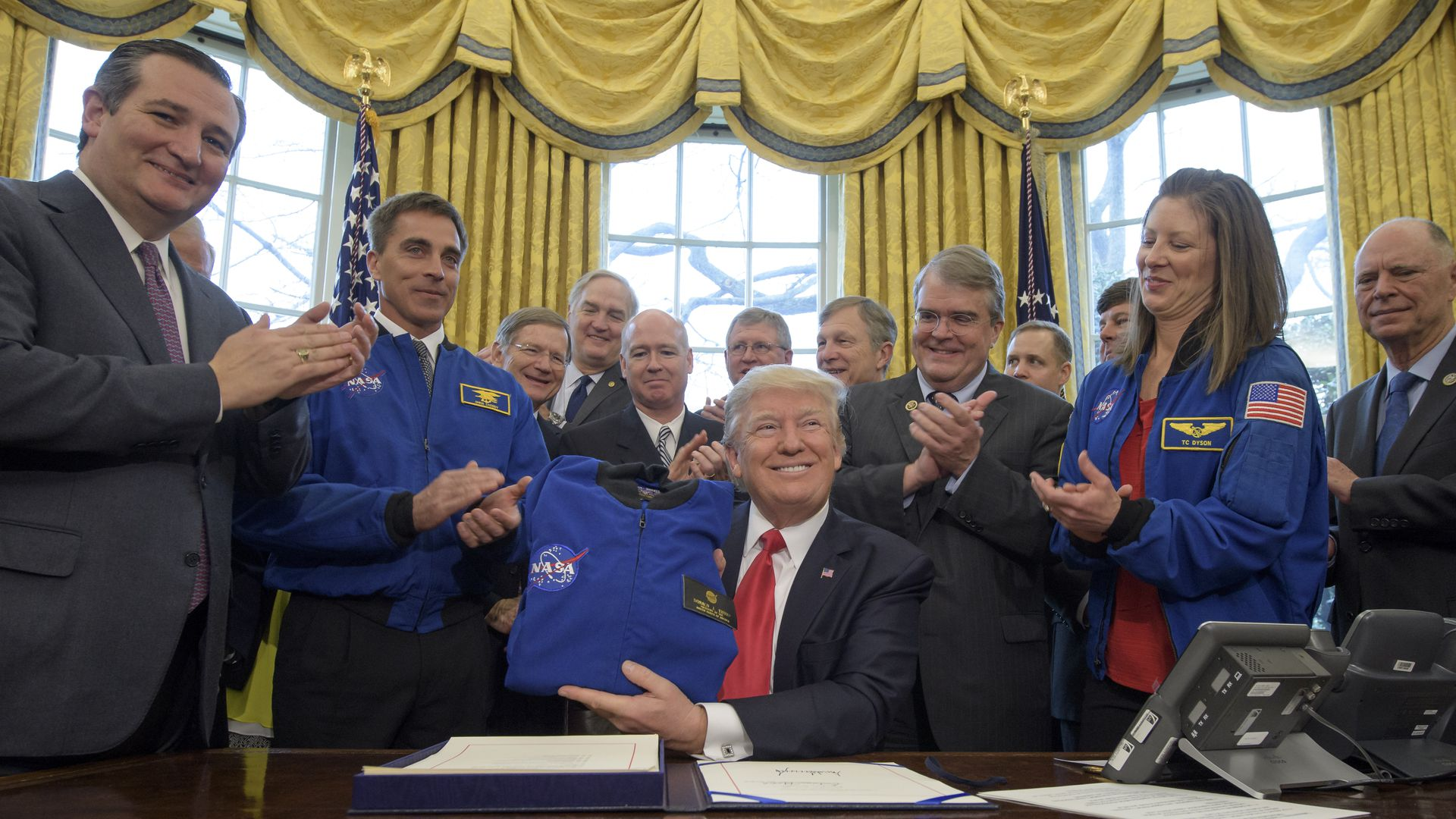 President Trump sits behind a desk, surrounded by NASA staff and Ted Cruz. Trump is holding a NASA launch jacket that he has just been gifted.