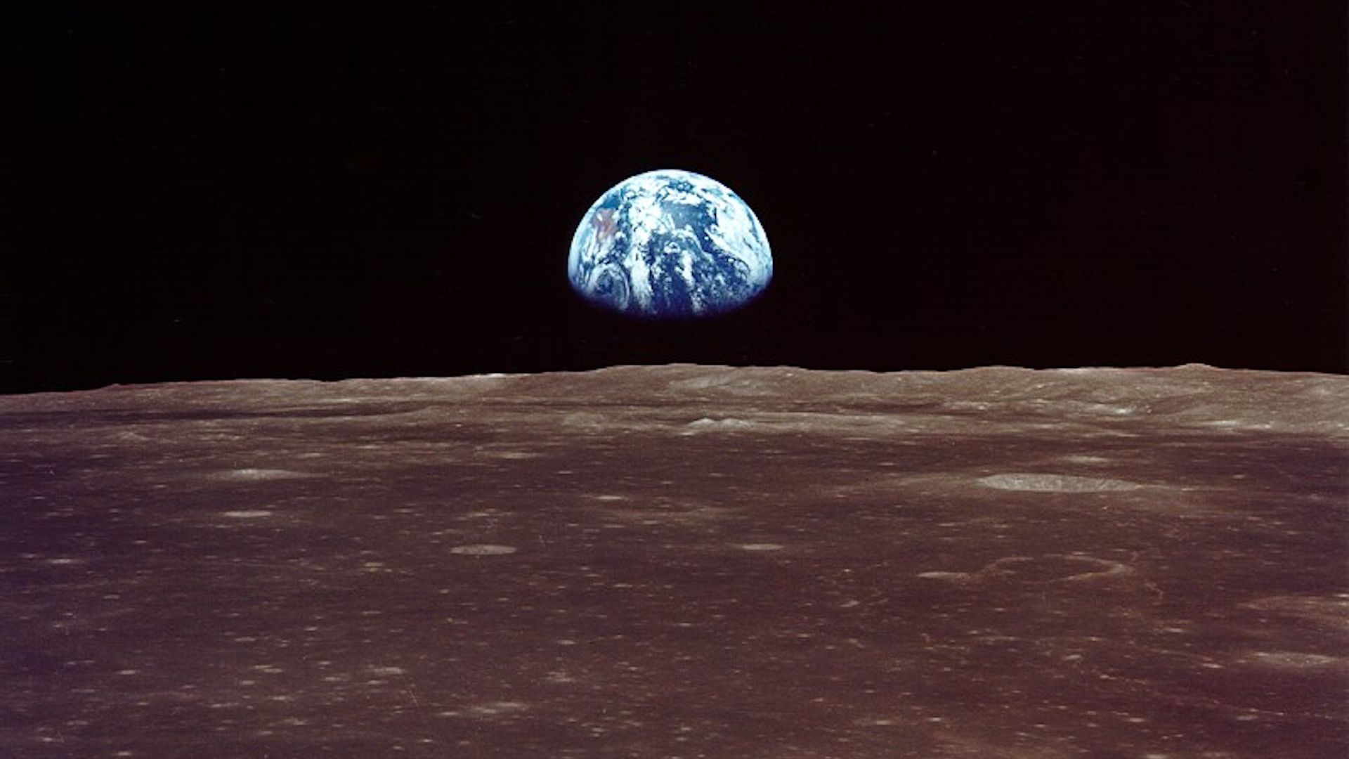 The Earth appearing over the limb of the Moon.