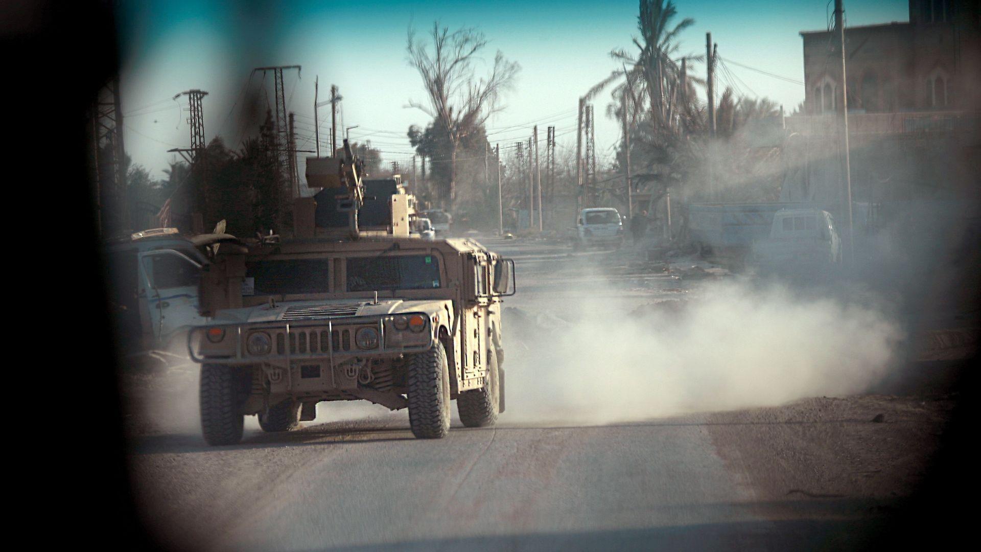 U.S. military vehicle driving through Syrian town.