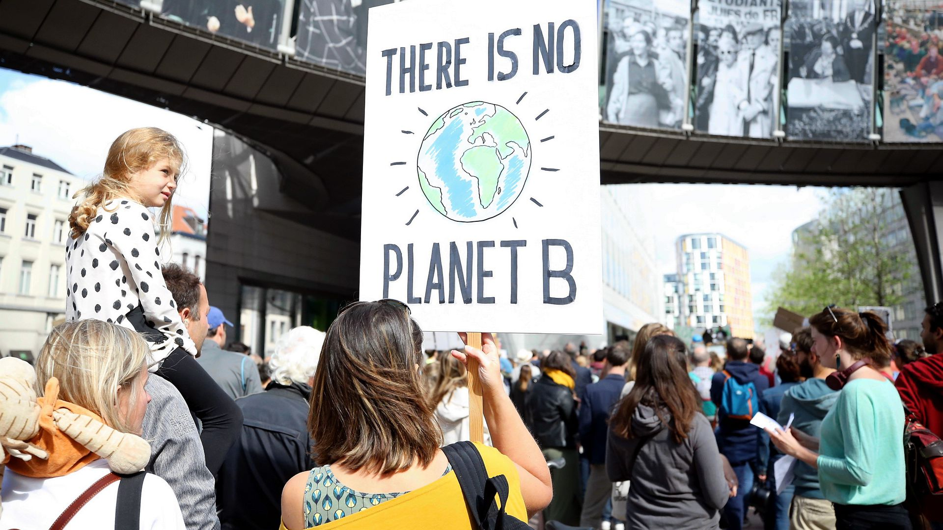 "Demonstrators walking, one holding a sign that reads ""There is no planet B"""