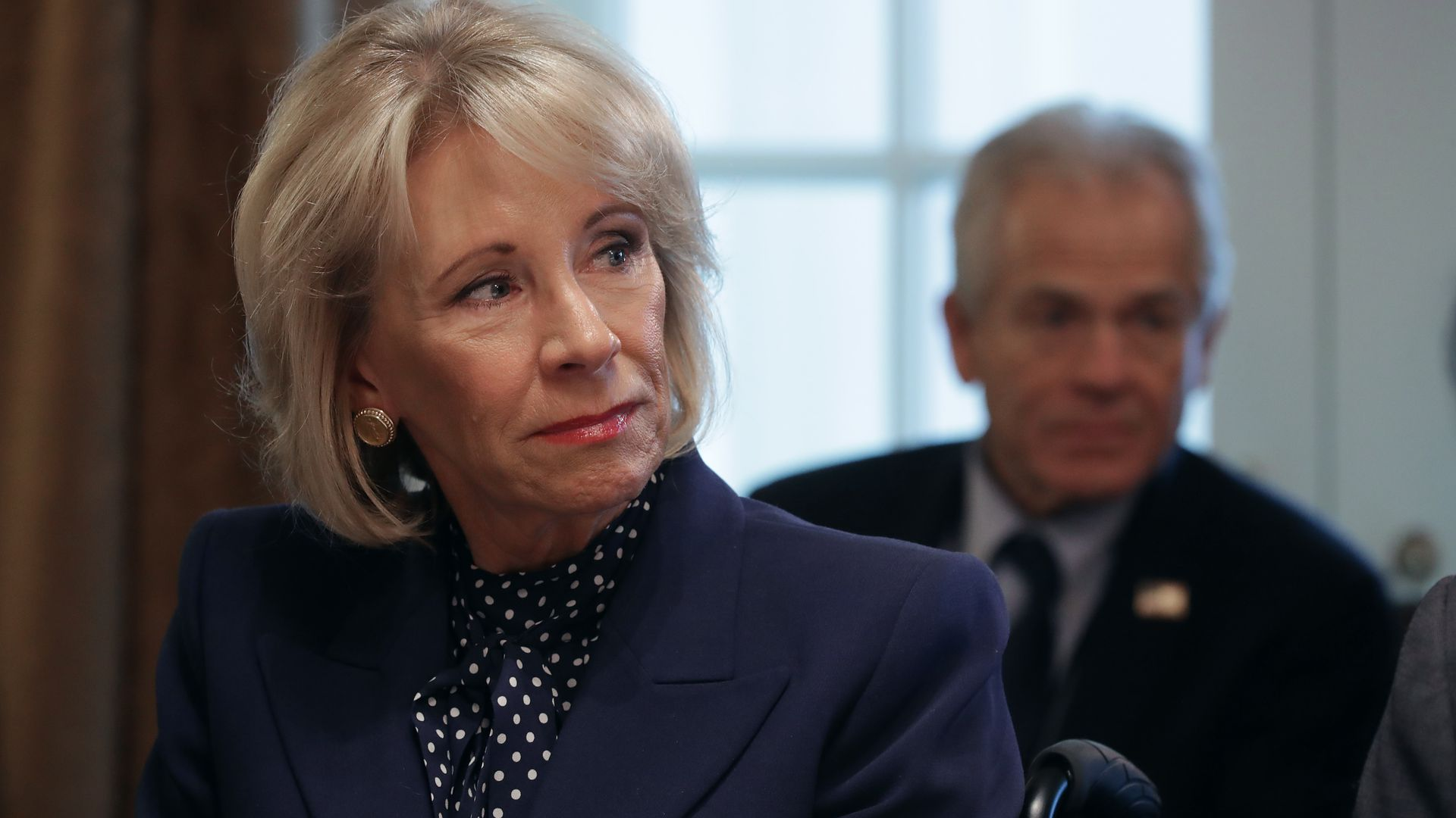 Education Secretary Betsy DeVos sits in a blue suit in a cabinet meeting.