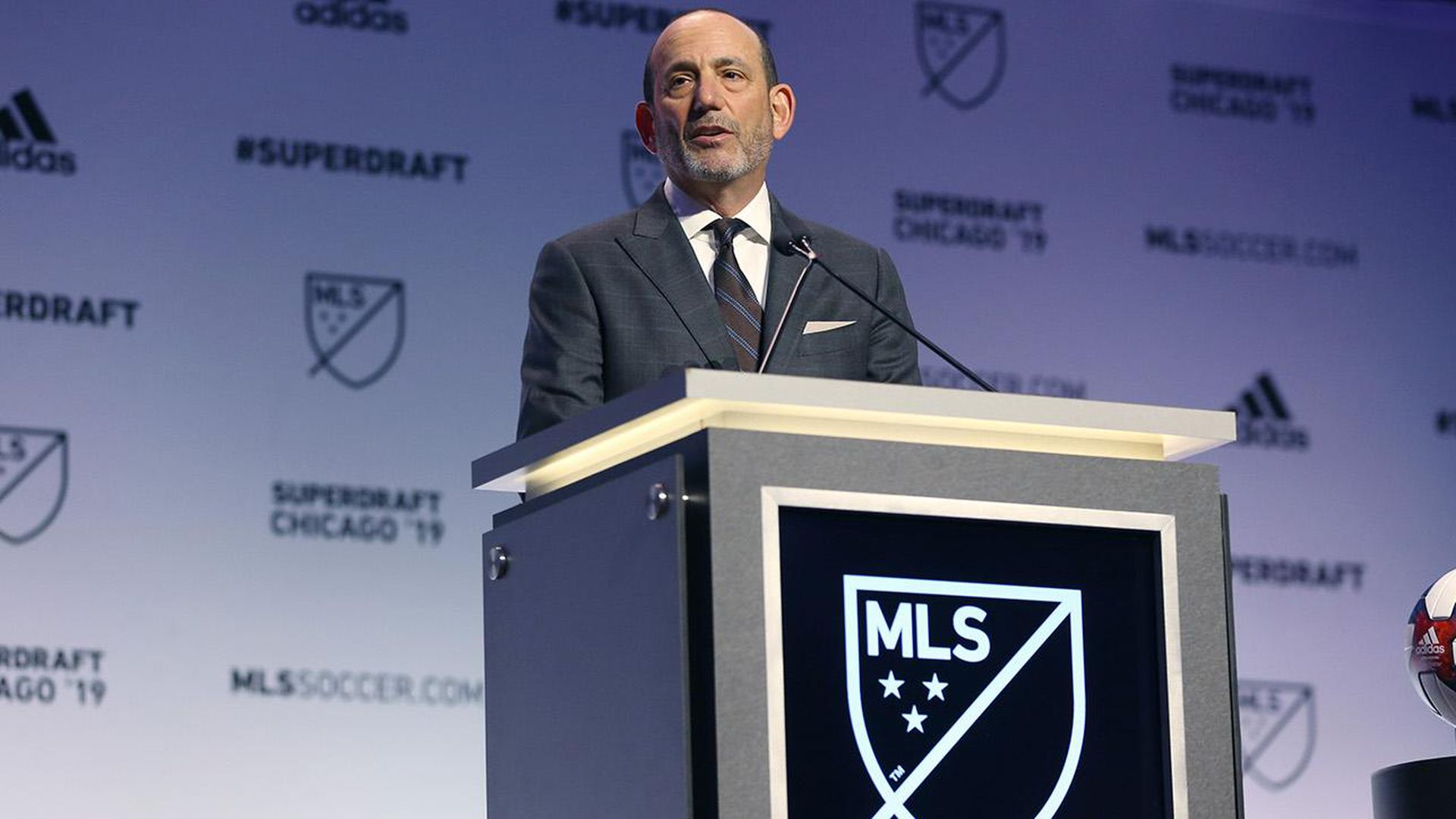 In this image, Don Garber stands in a suit and speaks from behind a podium.