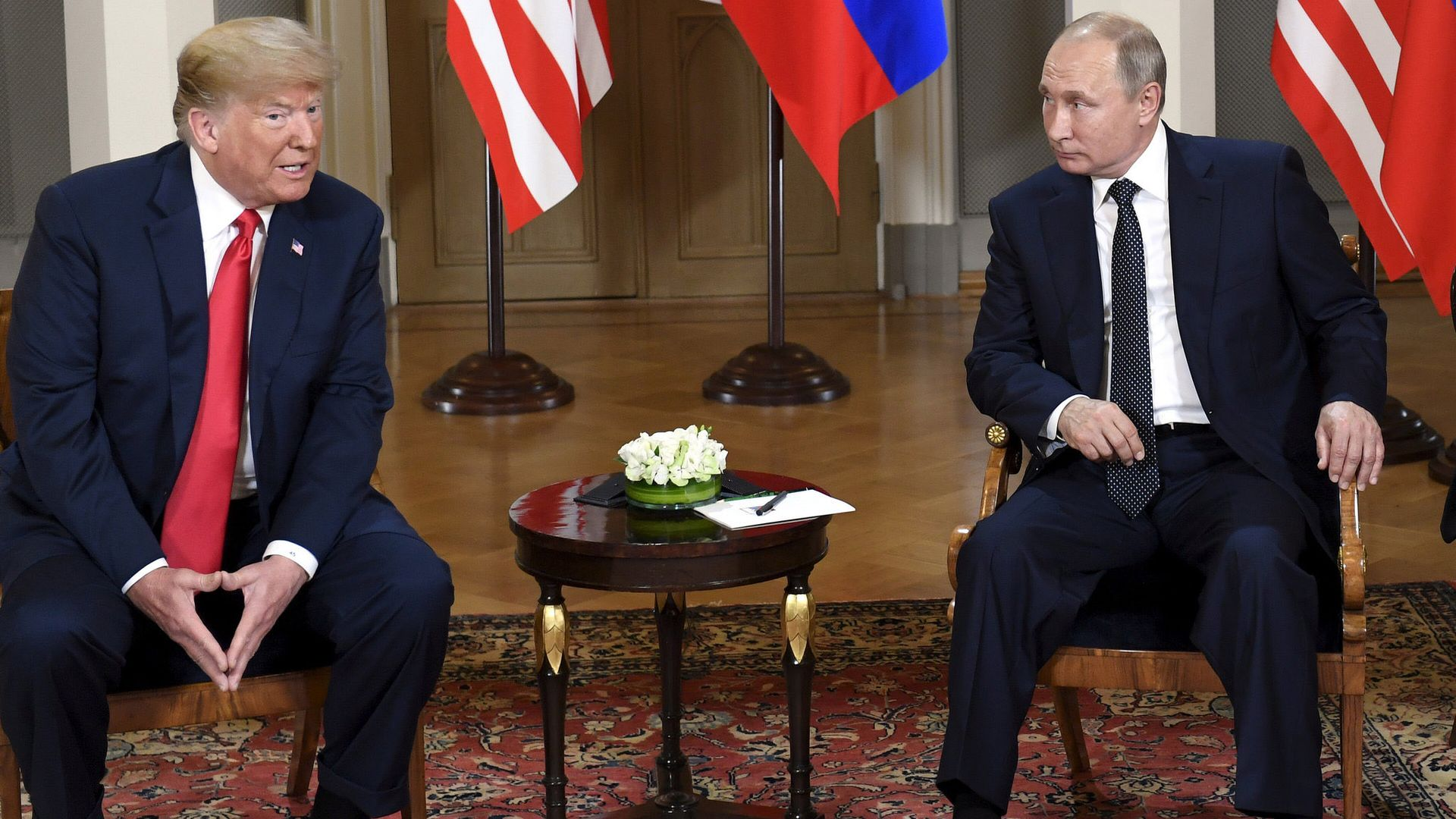 President trump and President putin sitting in chairs next to each other.