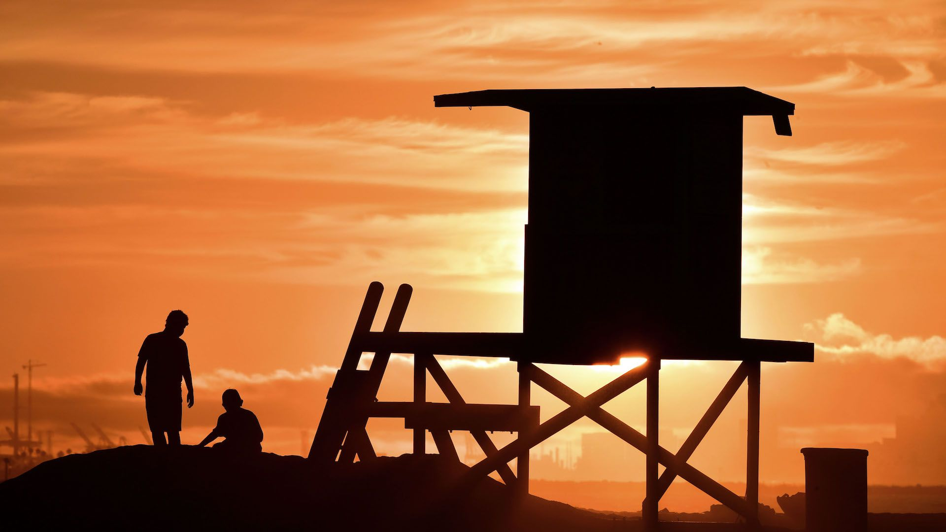 Children play beside a lifeguard tower as sunset approaches at Sunset Beach in Huntington Beach, California on July 21, 2018.