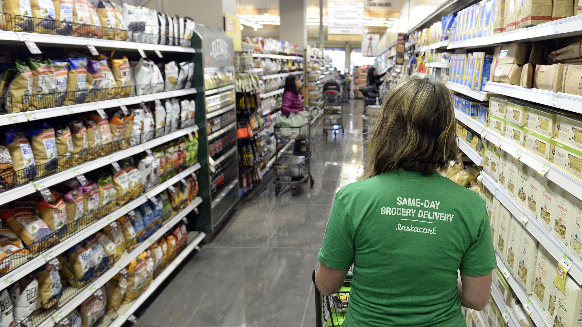 Instacart shopper in a grocery aisle.