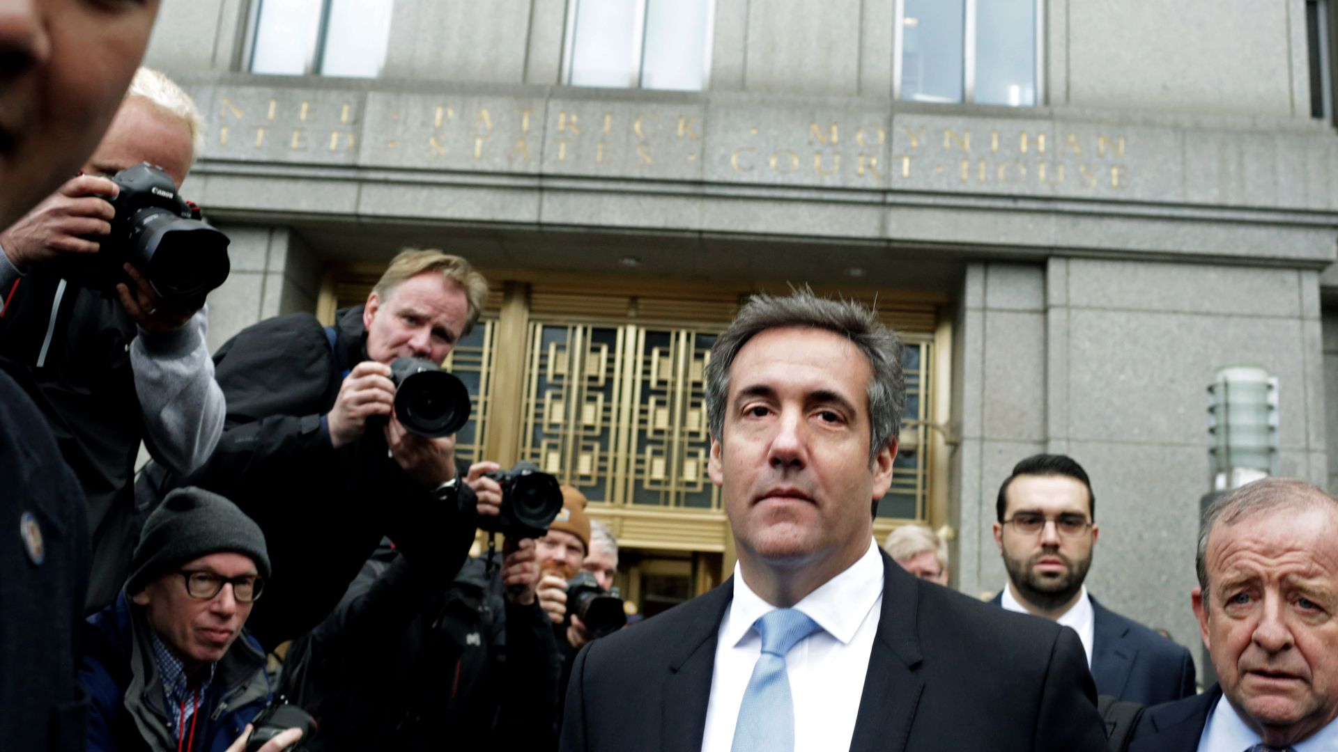 Michael Cohen walking next to photographers.