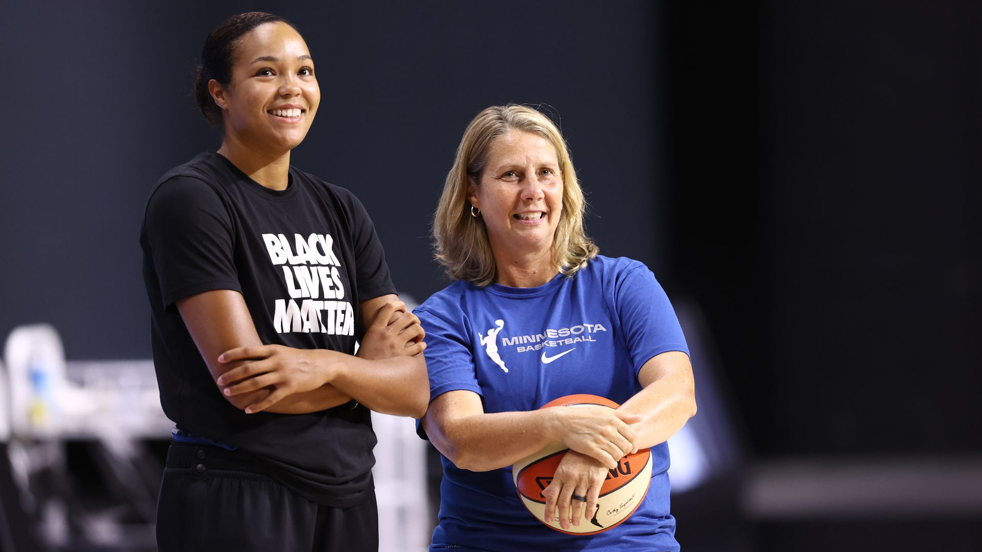 Cheryl Reeve wears a blue shirt and holds a basketball next to Napheesa Collier