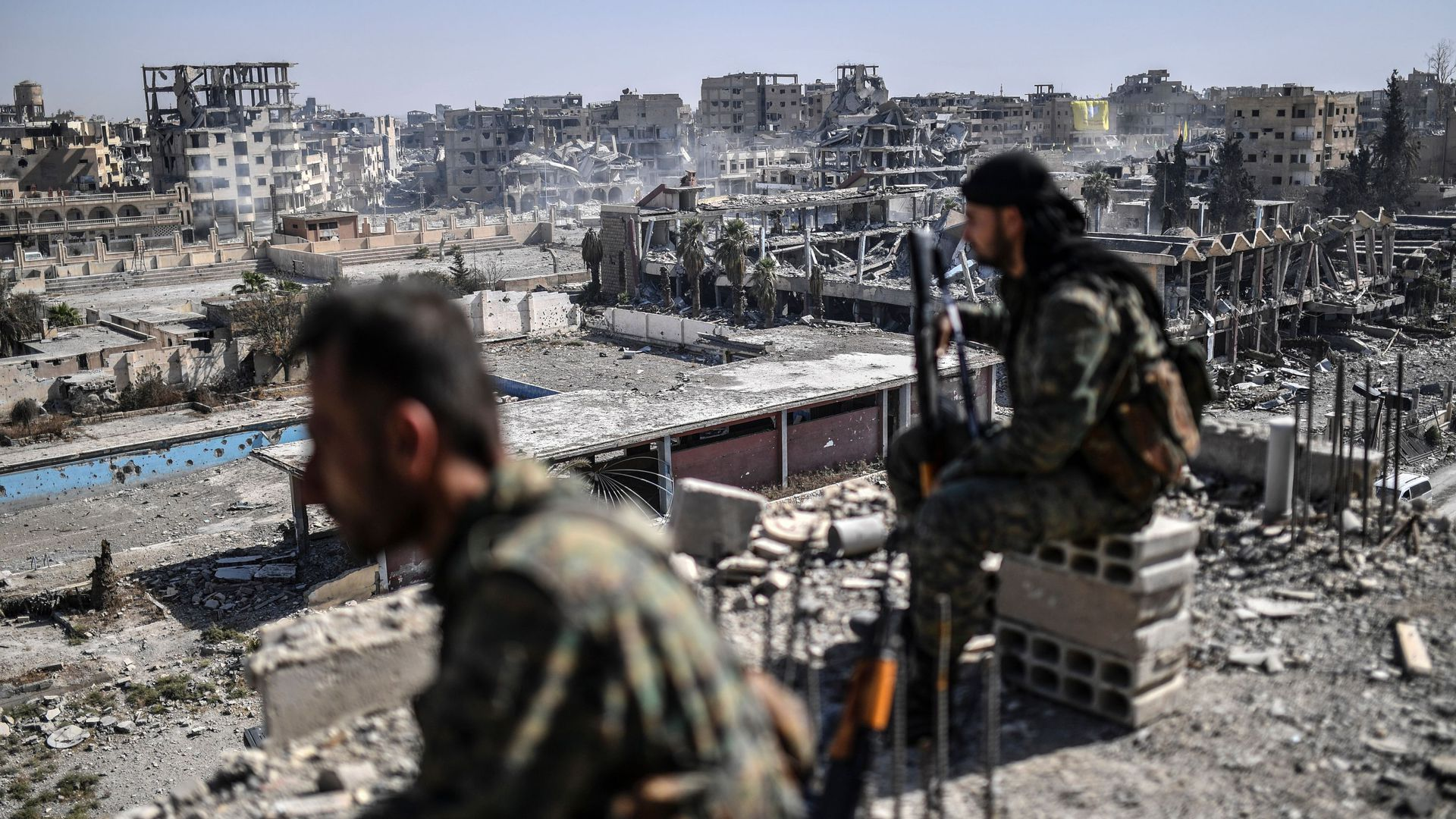 Fighters of the Syrian Democratic Forces (SDF) stand guard on a rooftop.
