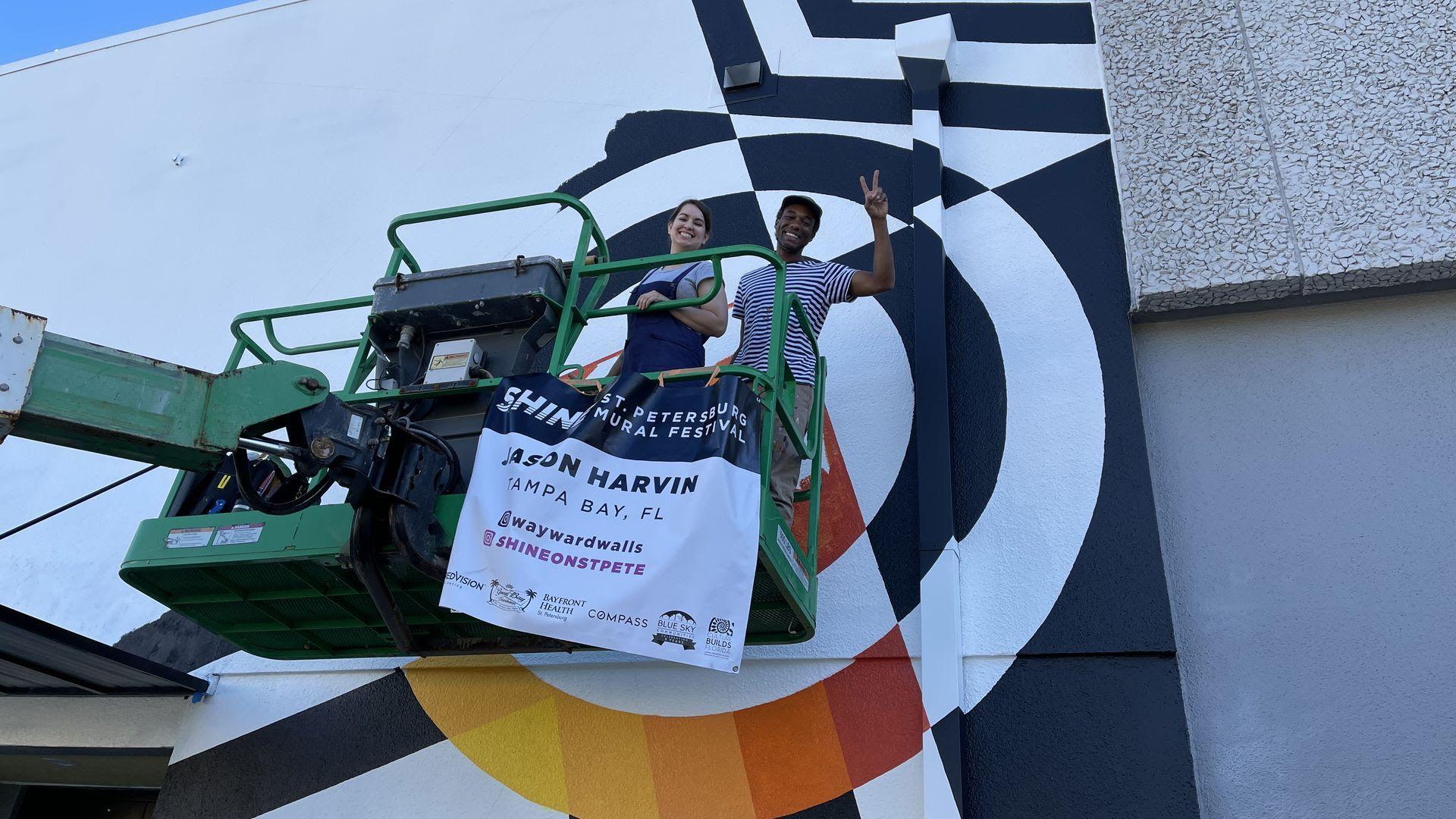 Vera Herrera and Jason Harvin work on his SHINE mural festival piece.