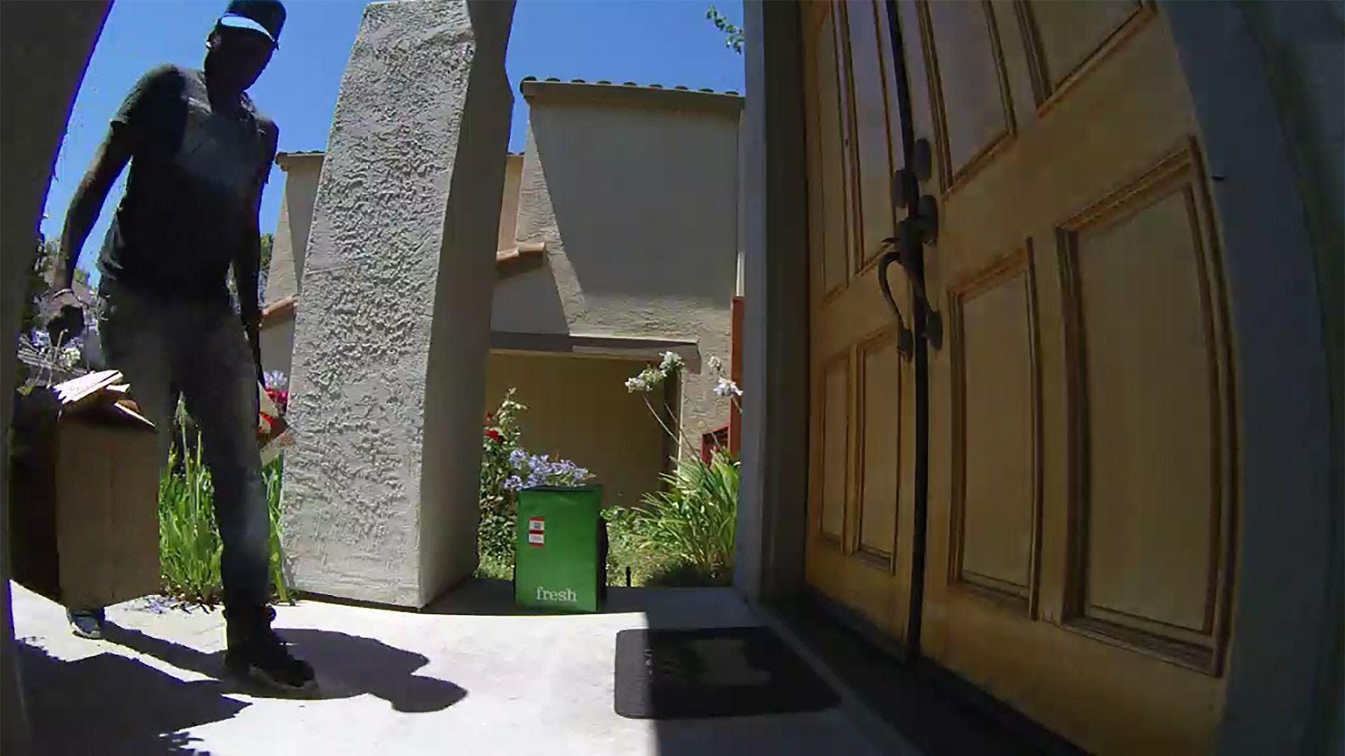 A man delivers a package to a door.