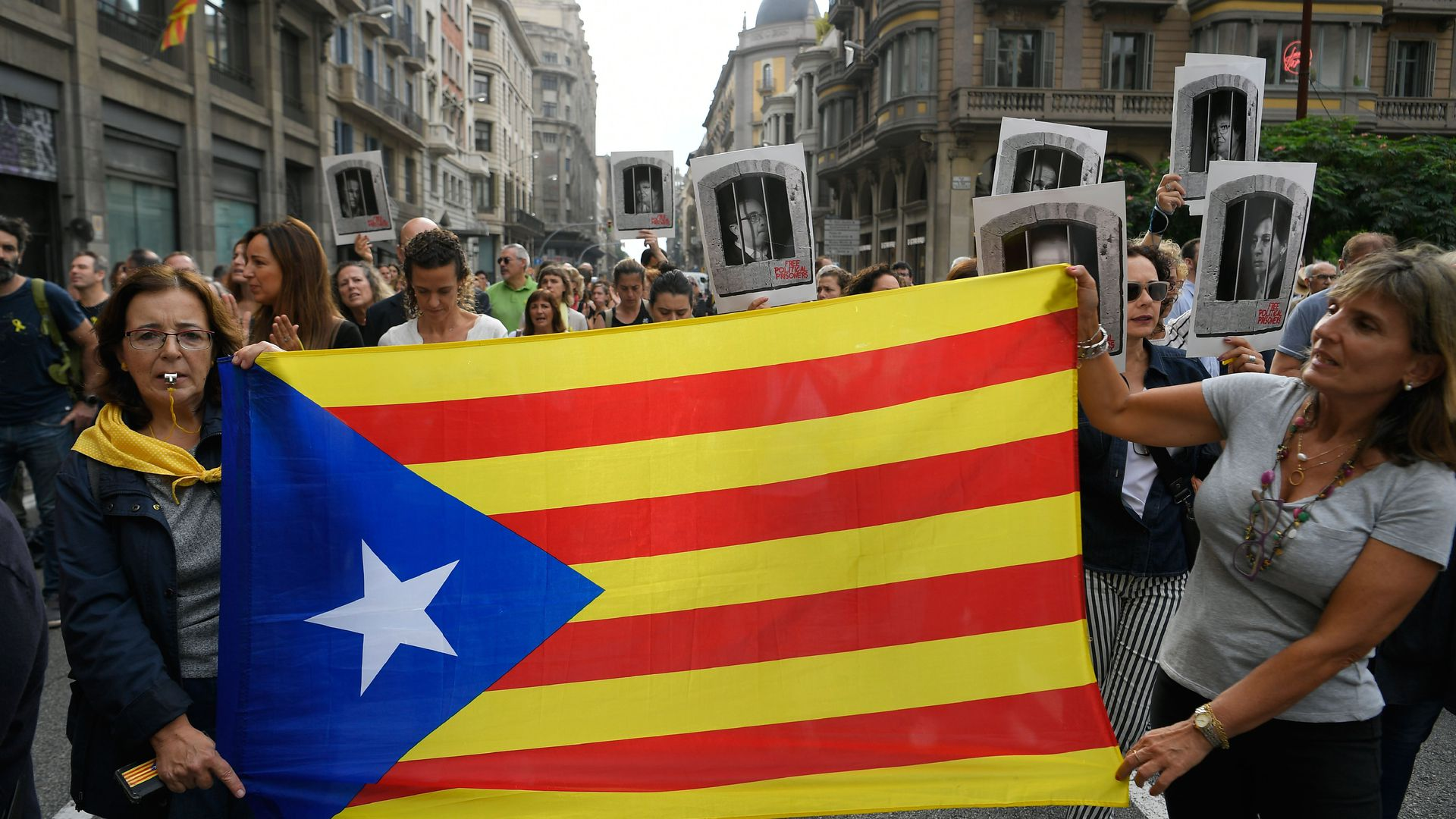 "Women hold a Catalan pro-independence ""Estelada"" flag in Barcelona on October 14"