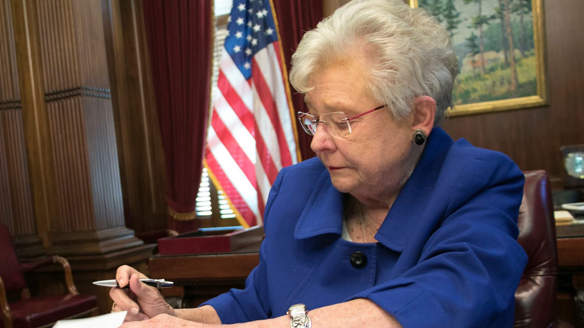 Alabama Gov. Kay Ivey signs a book.