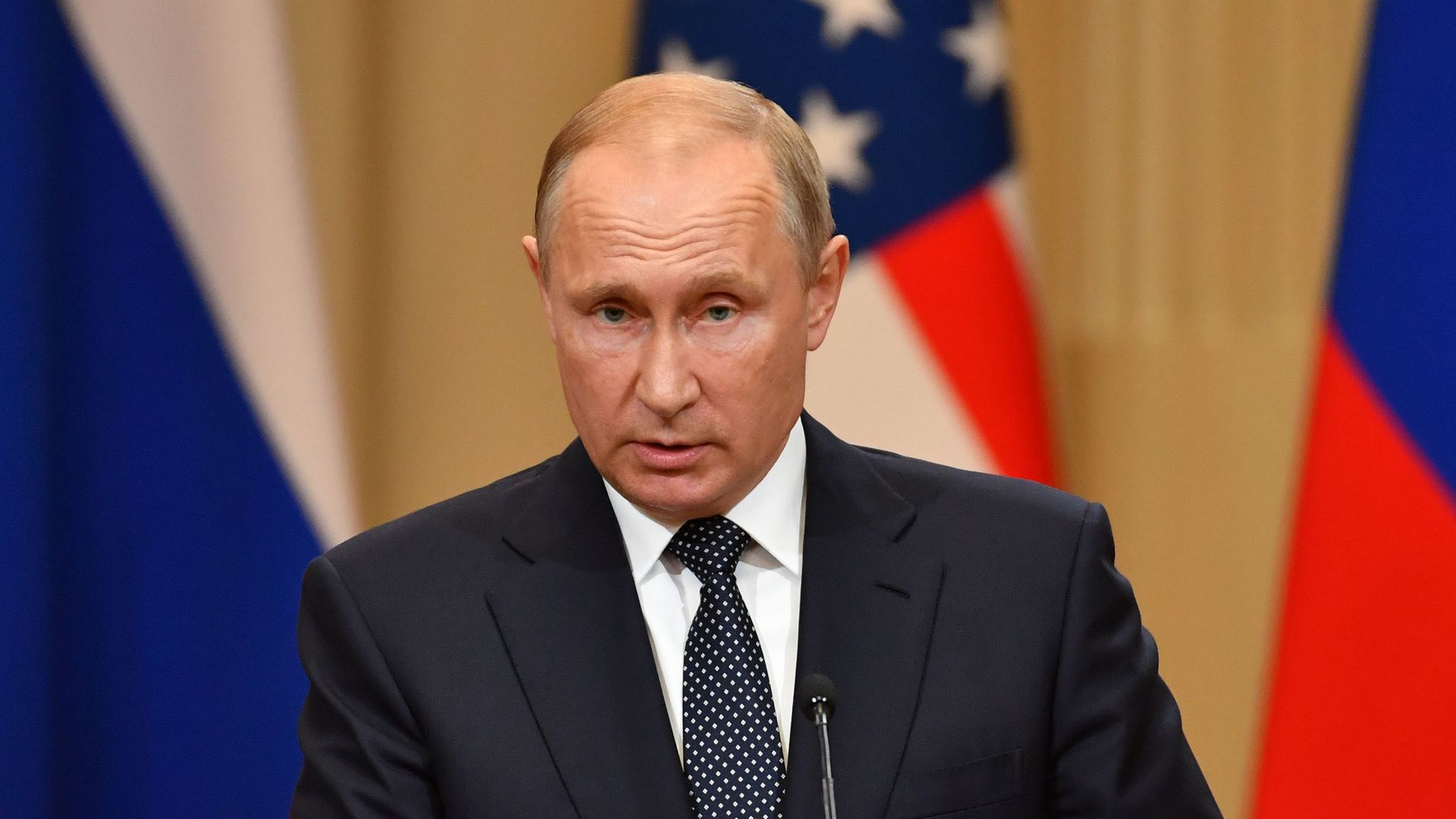 Vladimir Putin looks caught off guard, standing at a podium before a U.S. flag.