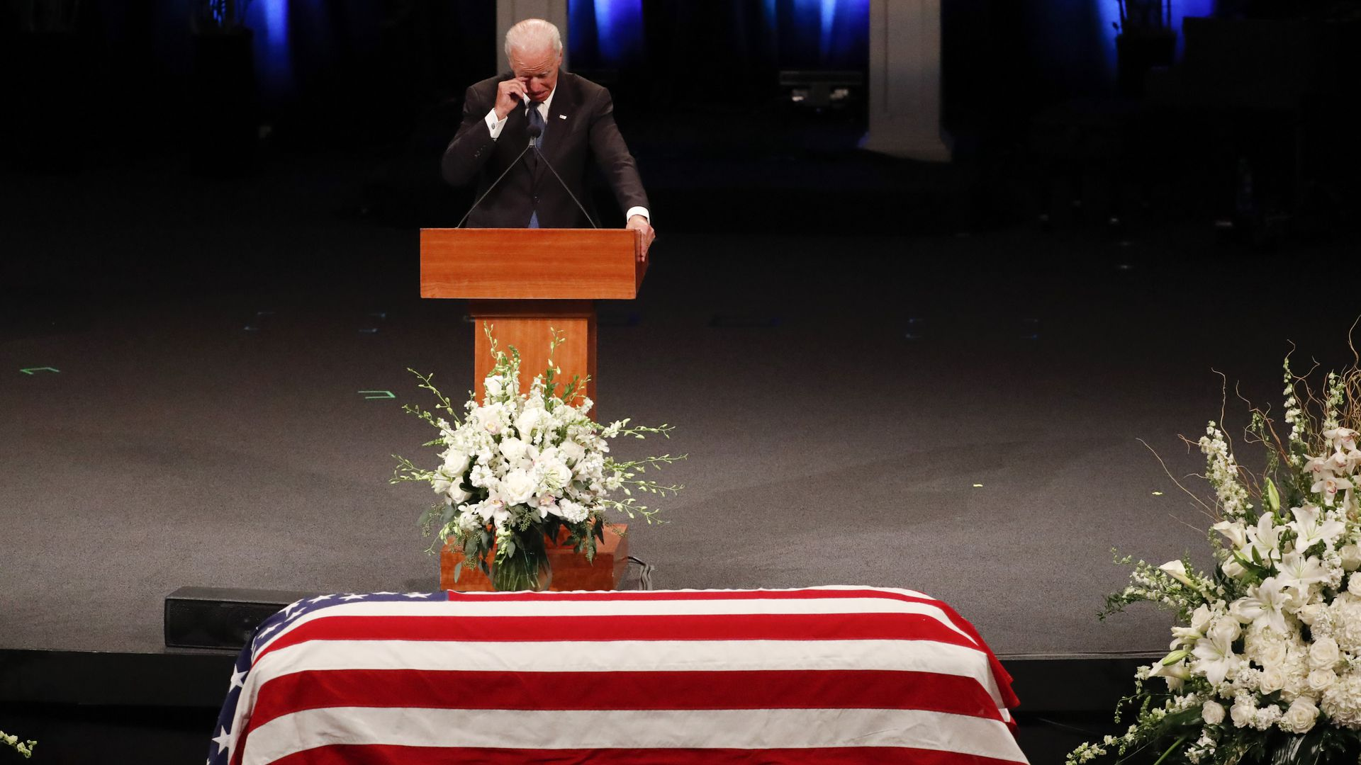 Joe Biden touches his face while crying standing at podium before McCain's casket covered in American flag