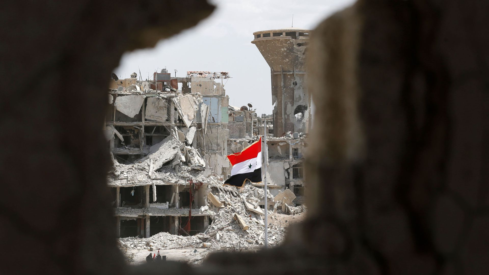A Syrian flag flying amid rubble.