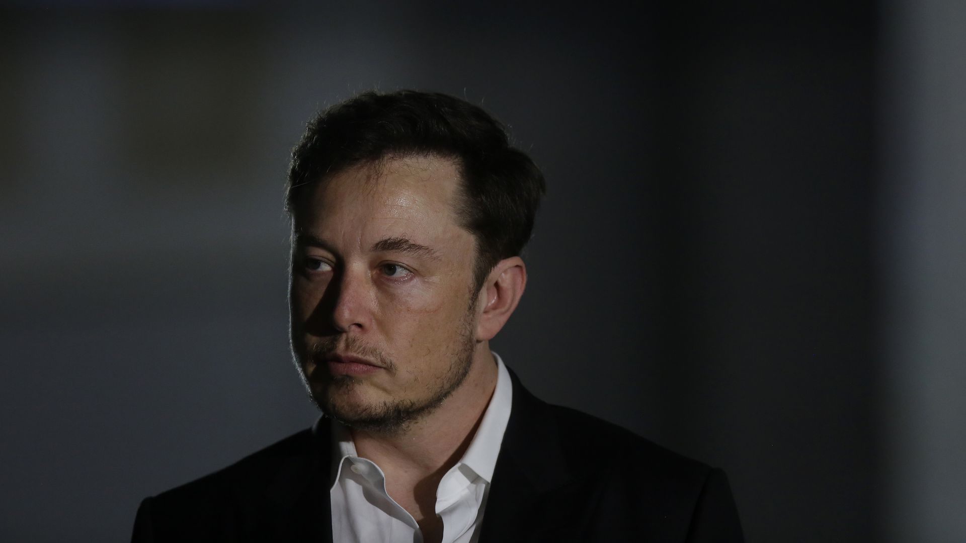 Close up of Elon Musk, who's wearing a serious expression