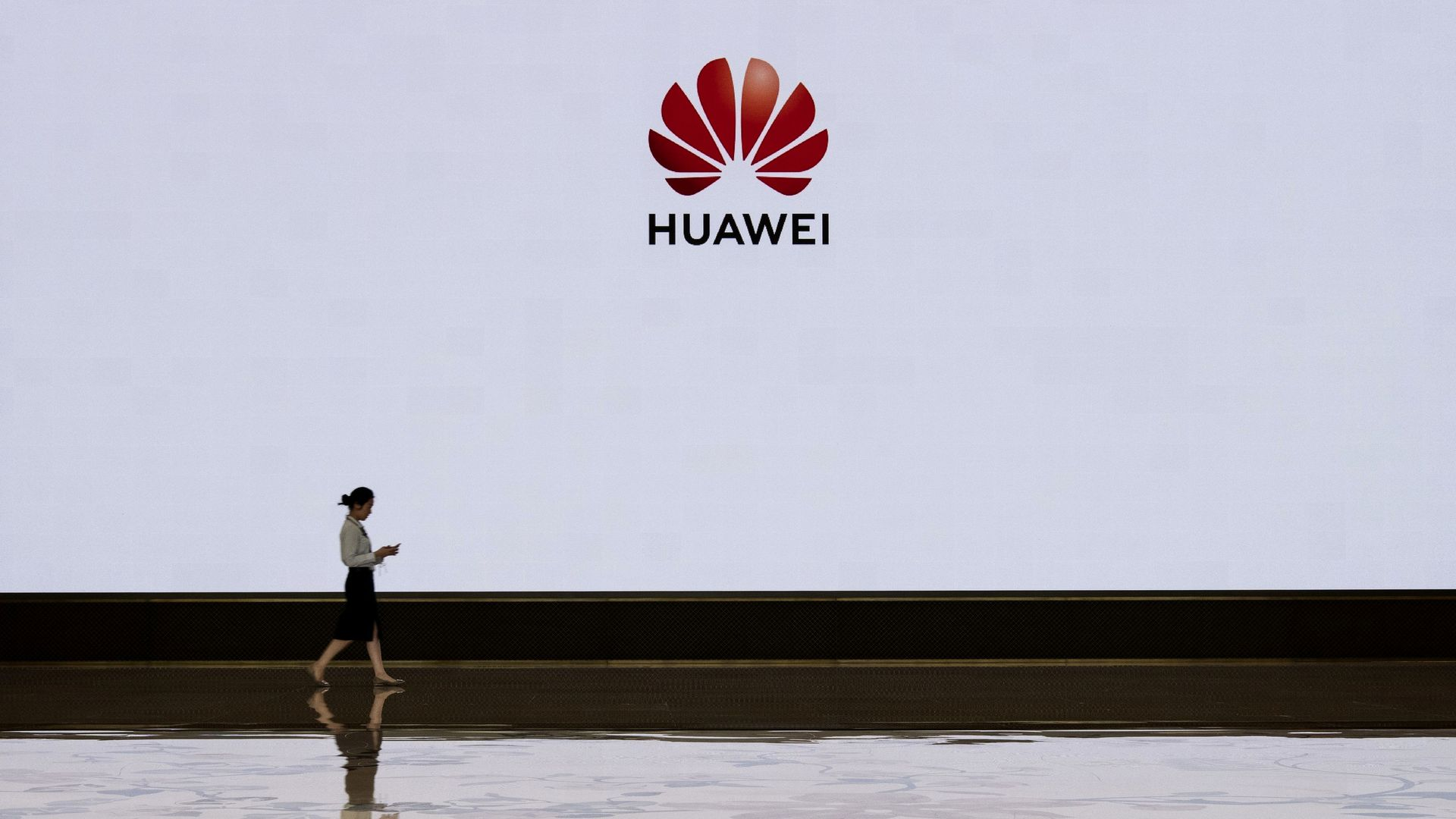 In this image, a woman walks by a large white wall that also includes the Huawei logo.