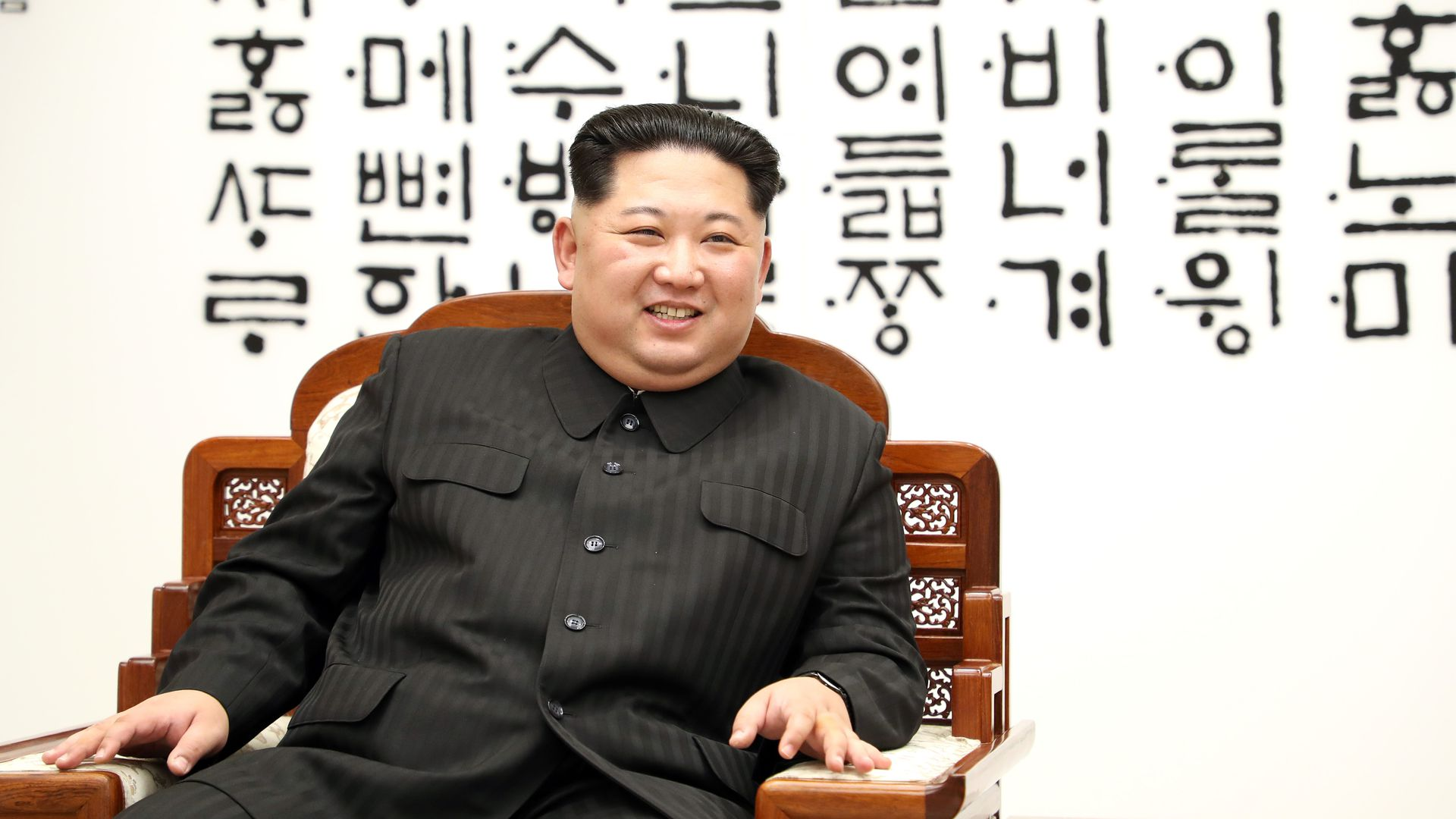 Kim Jong-un sits in chair smiling.