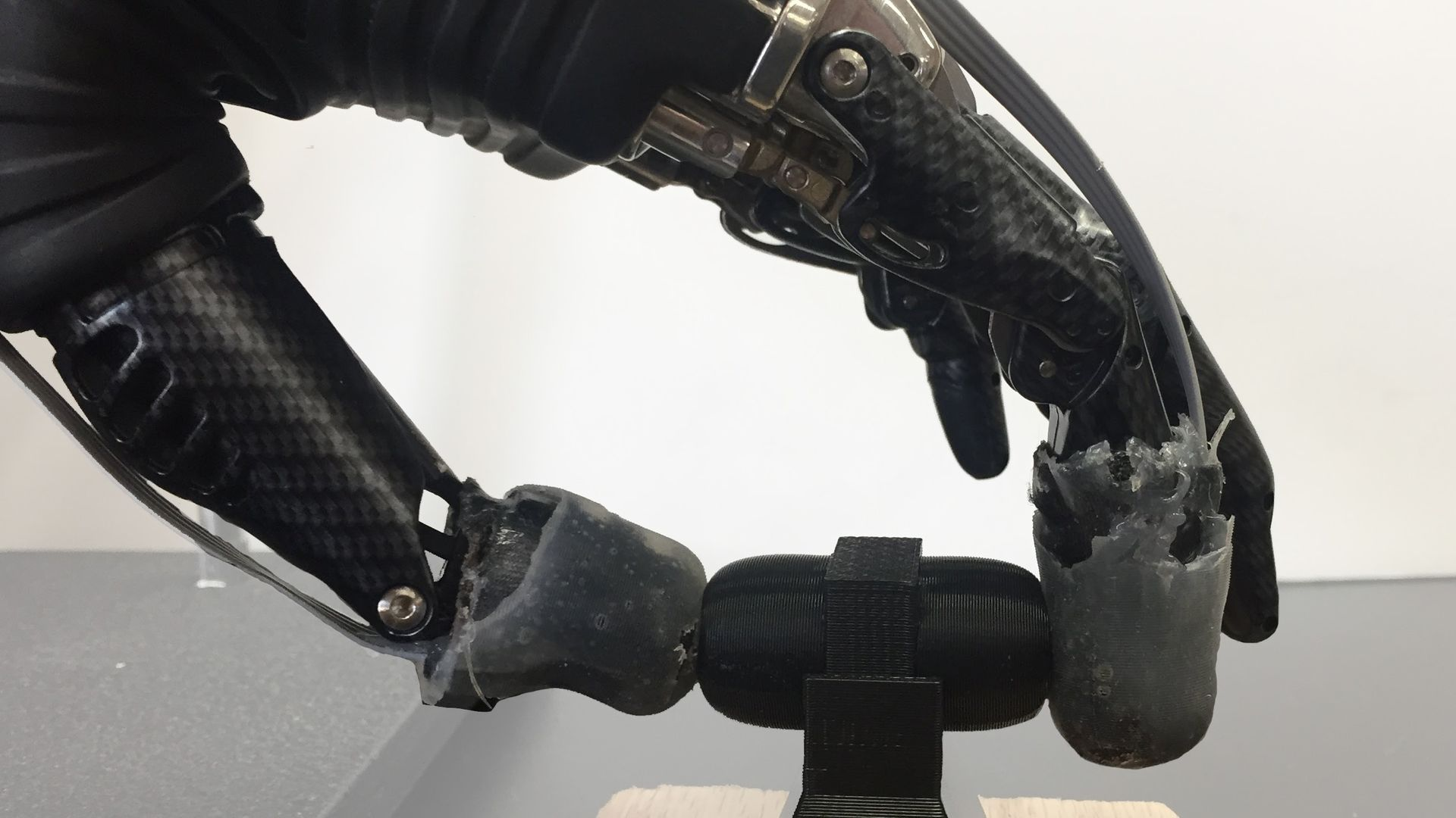 A prosthetic hand with e-dermis picks up an object