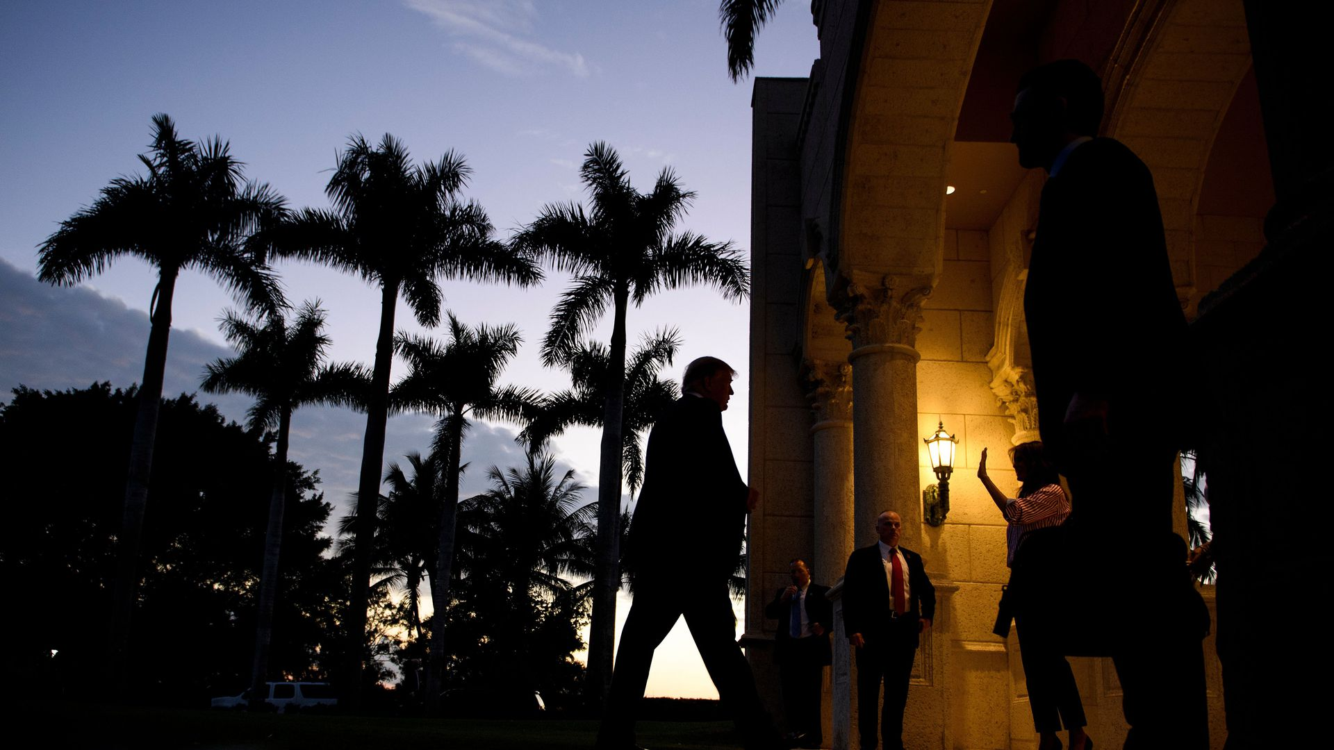 This photo shows Donald Trump walking in Florida, with palm trees in the background as the light fades.