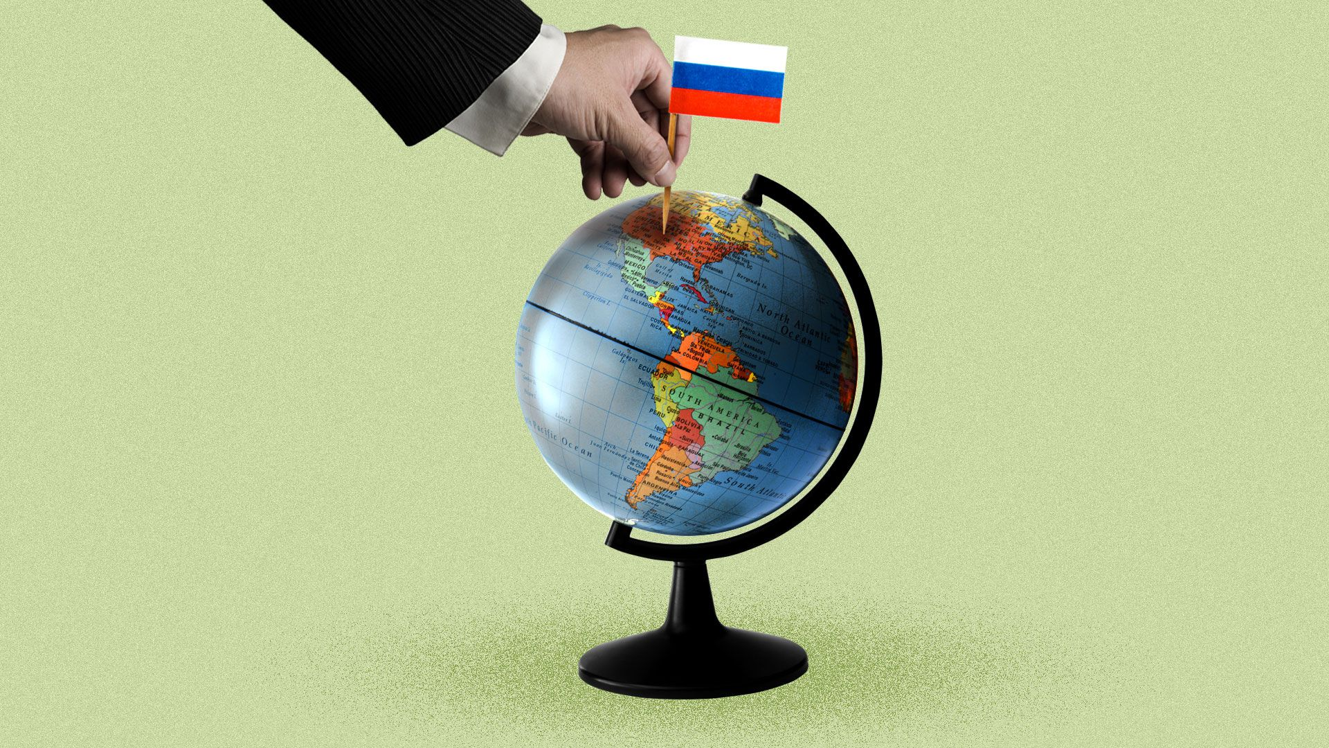 A hand planting a Russian flag on a globe