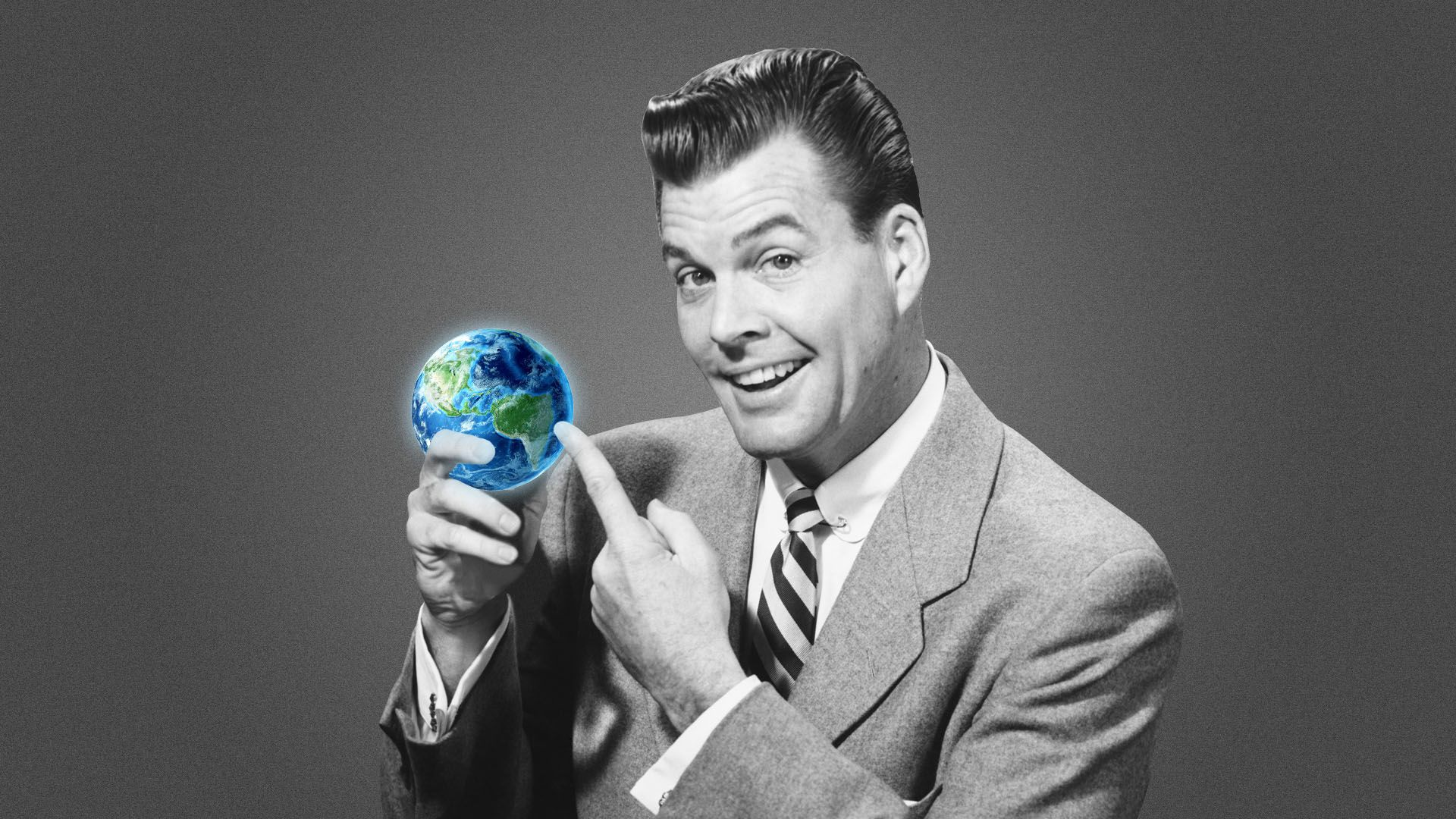 Man who looks like a corporate executive holding a small Earth-shaped ball and pointing to it.