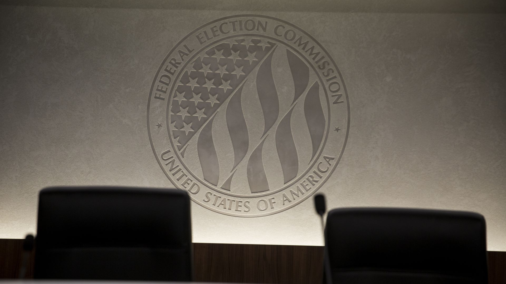 The federal election commission logo behind a set of empty chairs.