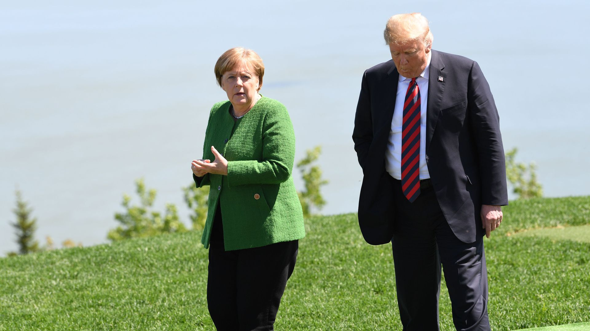 Angela Merkel in green and Trump in black walk on green grass looking serious before a body of water.