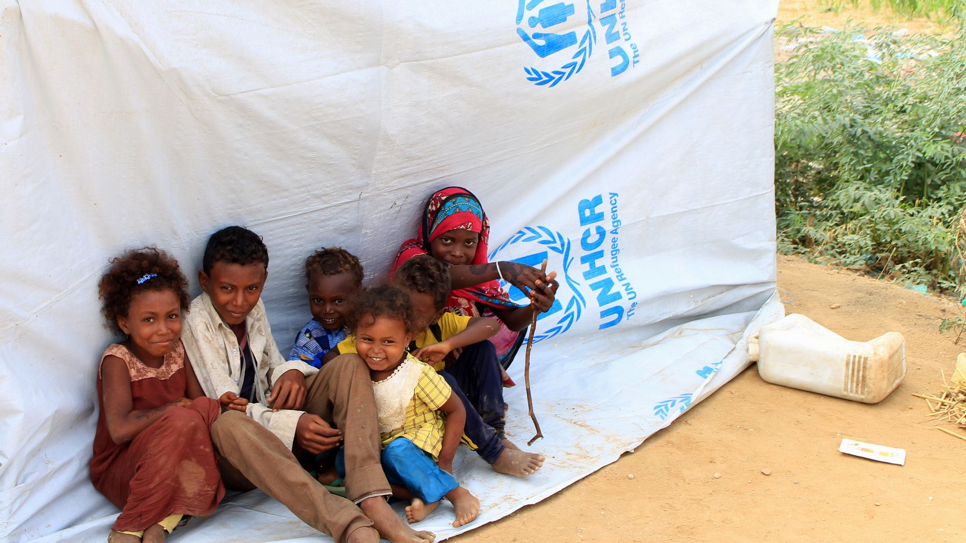 displaced Yemeni children sitting on a tarp