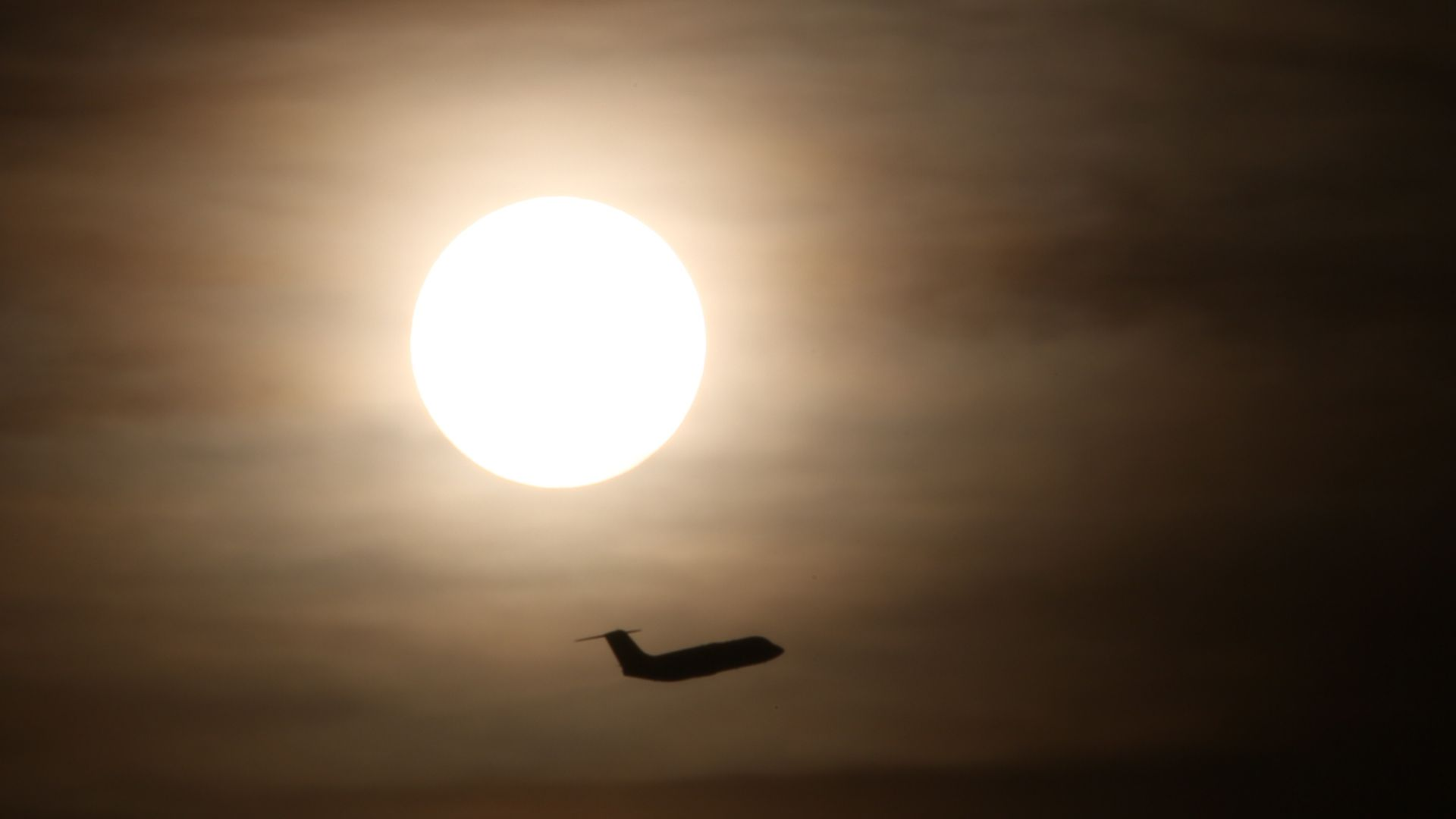 Plane flying across the sky with sun in the distance
