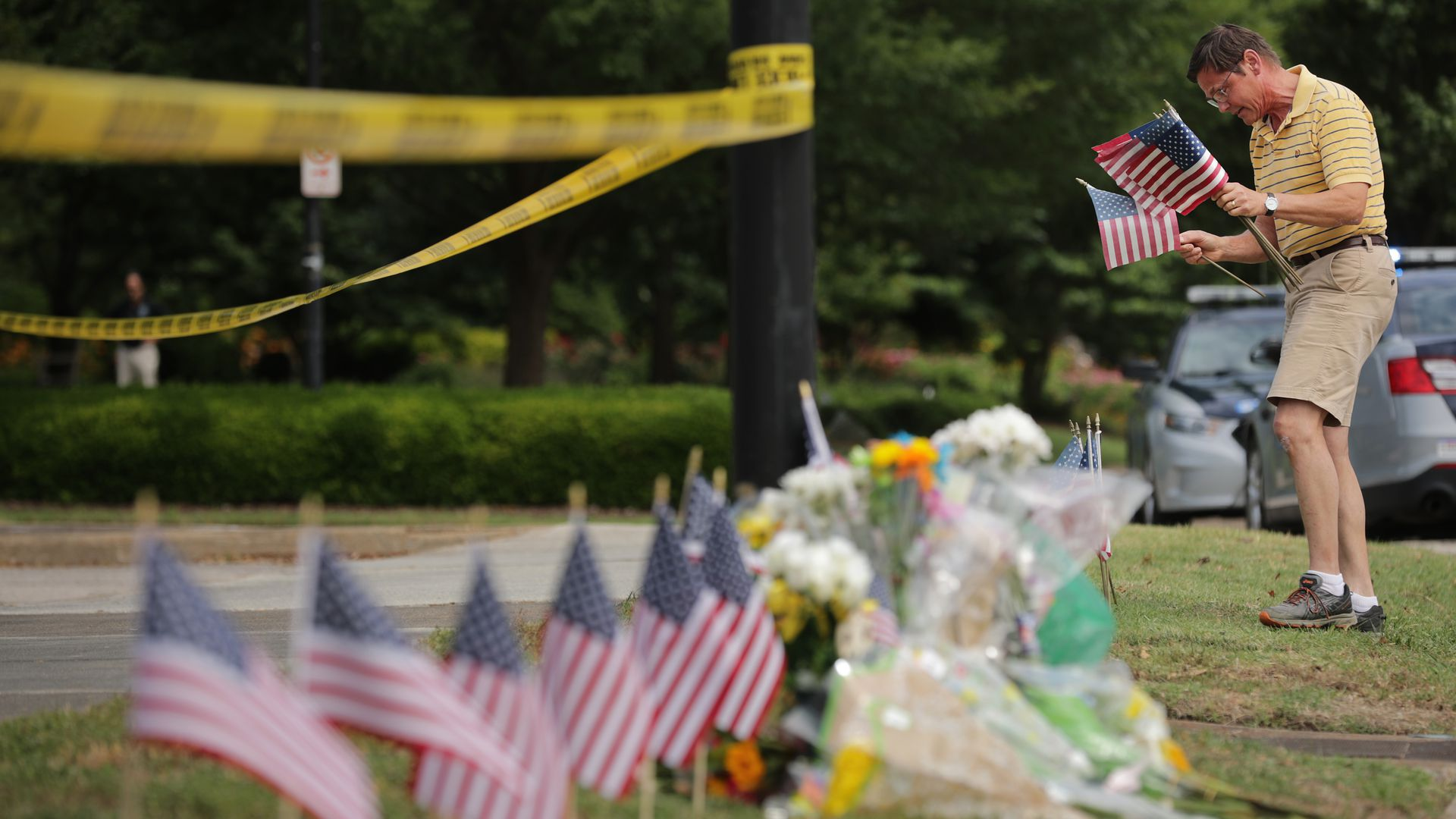 Rich Lindgren places 12 U.S. flags in the ground at a makeshif memorial outside of the crime scene at the Virginia Beach Municipal Center June 01, 2019 in Virginia Beach, Virginia.
