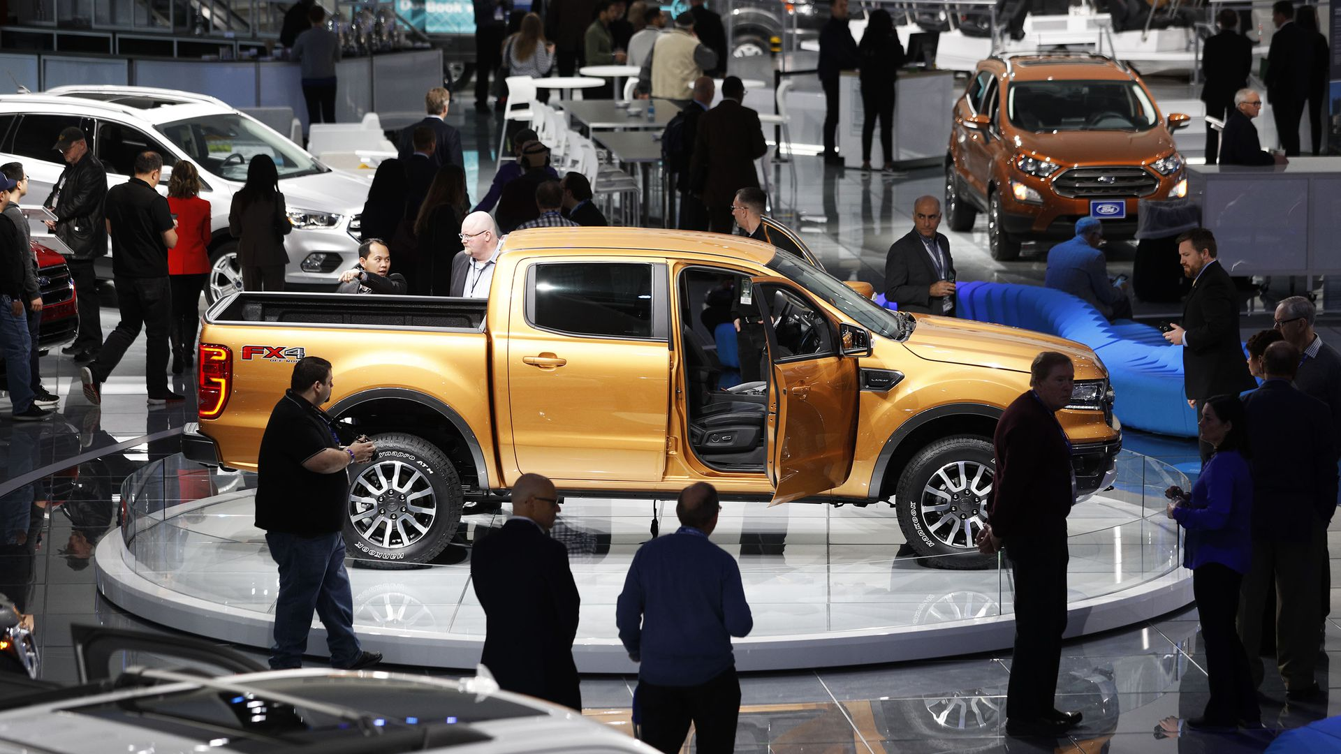 A truck amongst a crowd of people at the Detroit Auto Show