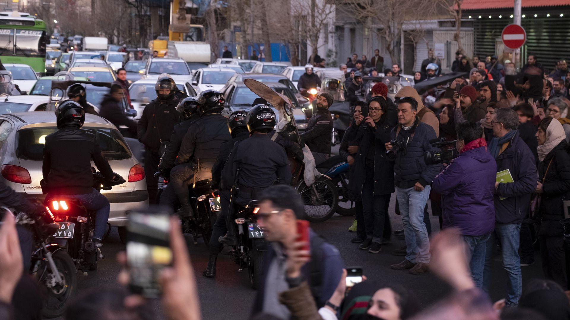 Anti-Riot policemen ride motorcycles along an avenue as Iranians gather