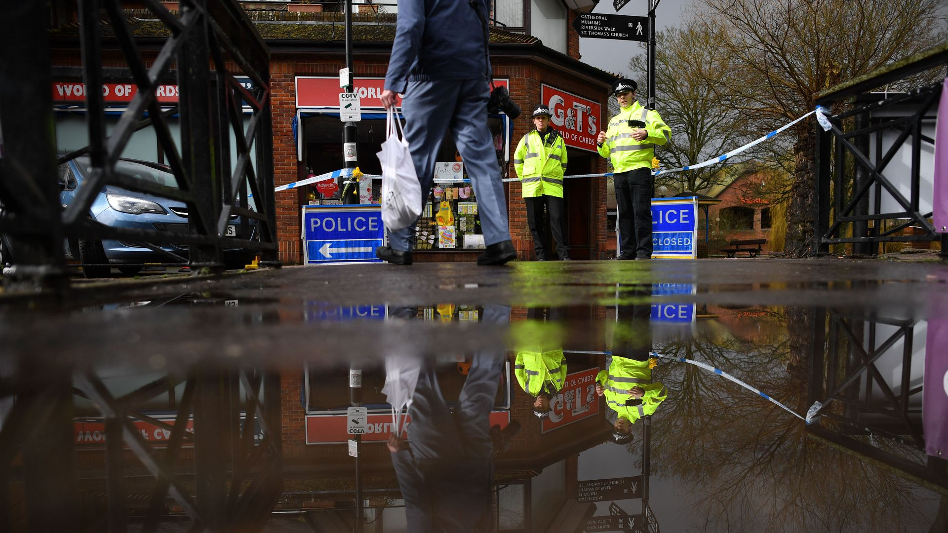 water on a sidewalk with british cops in the background