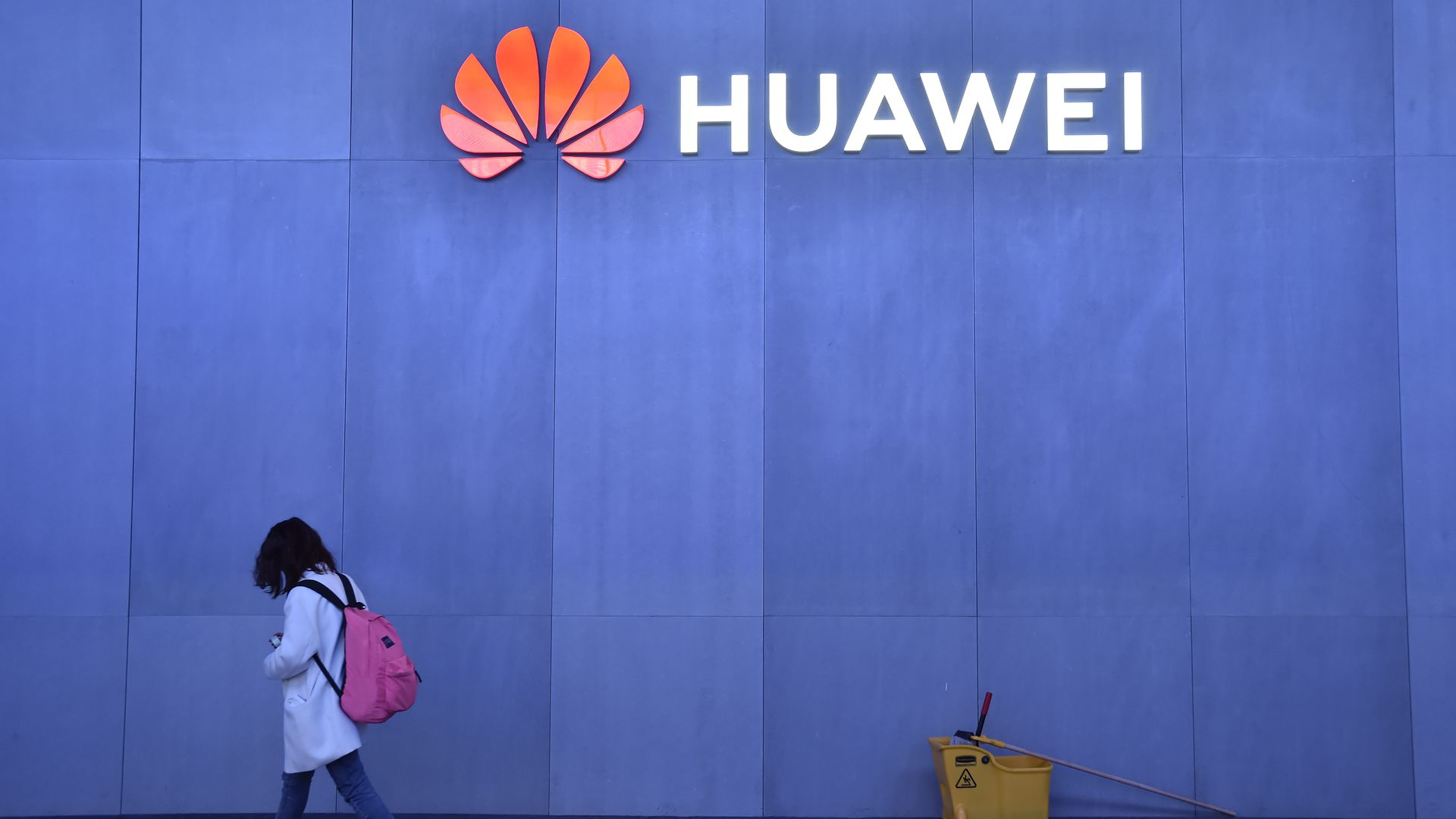 "A blue wall with a neon sign that says ""Huawei."" There is a young person wearing a backpack walking in front of the wall."
