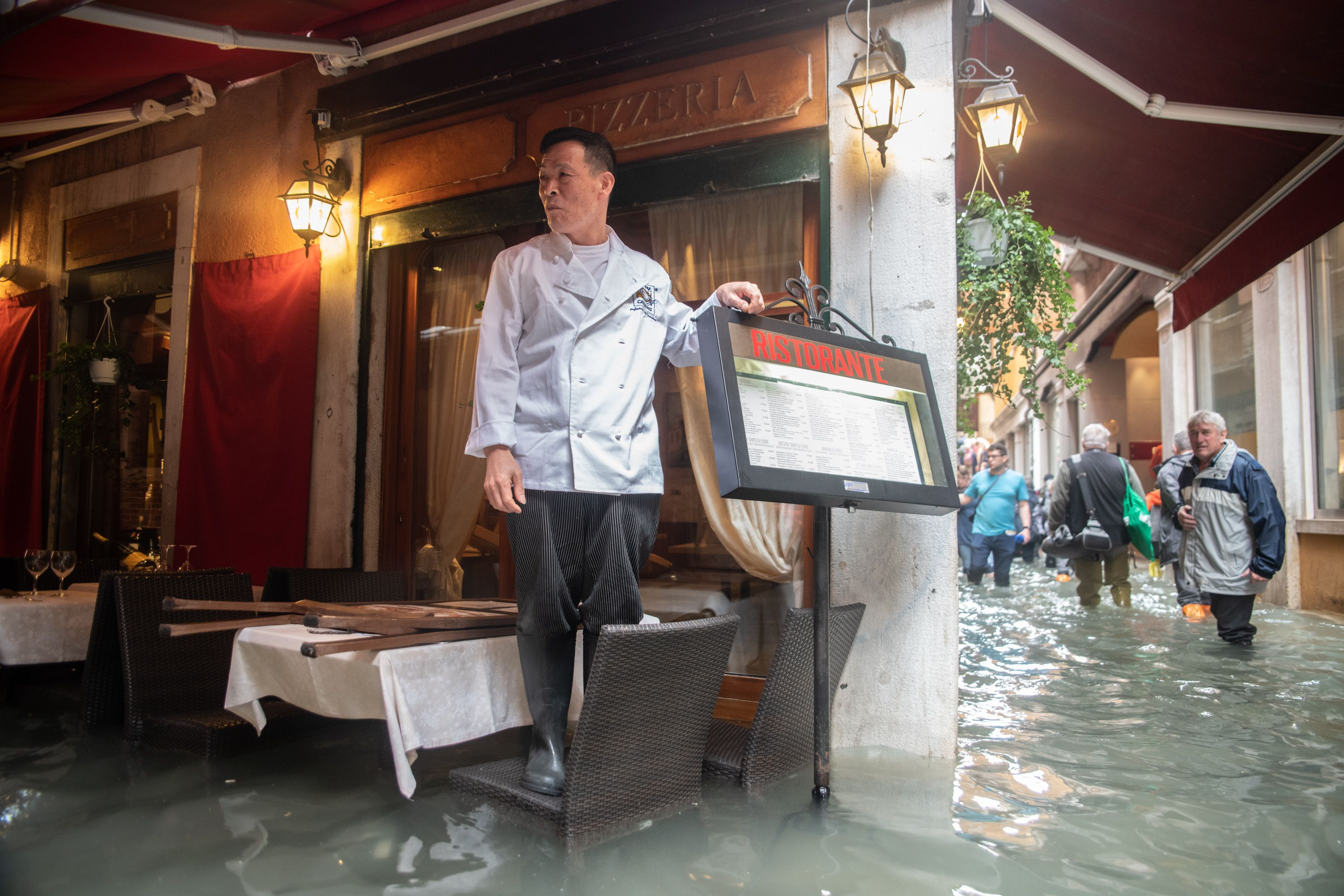 Man/restaurant owner standing on chair in restaurant to avoid flooded waters in venice.