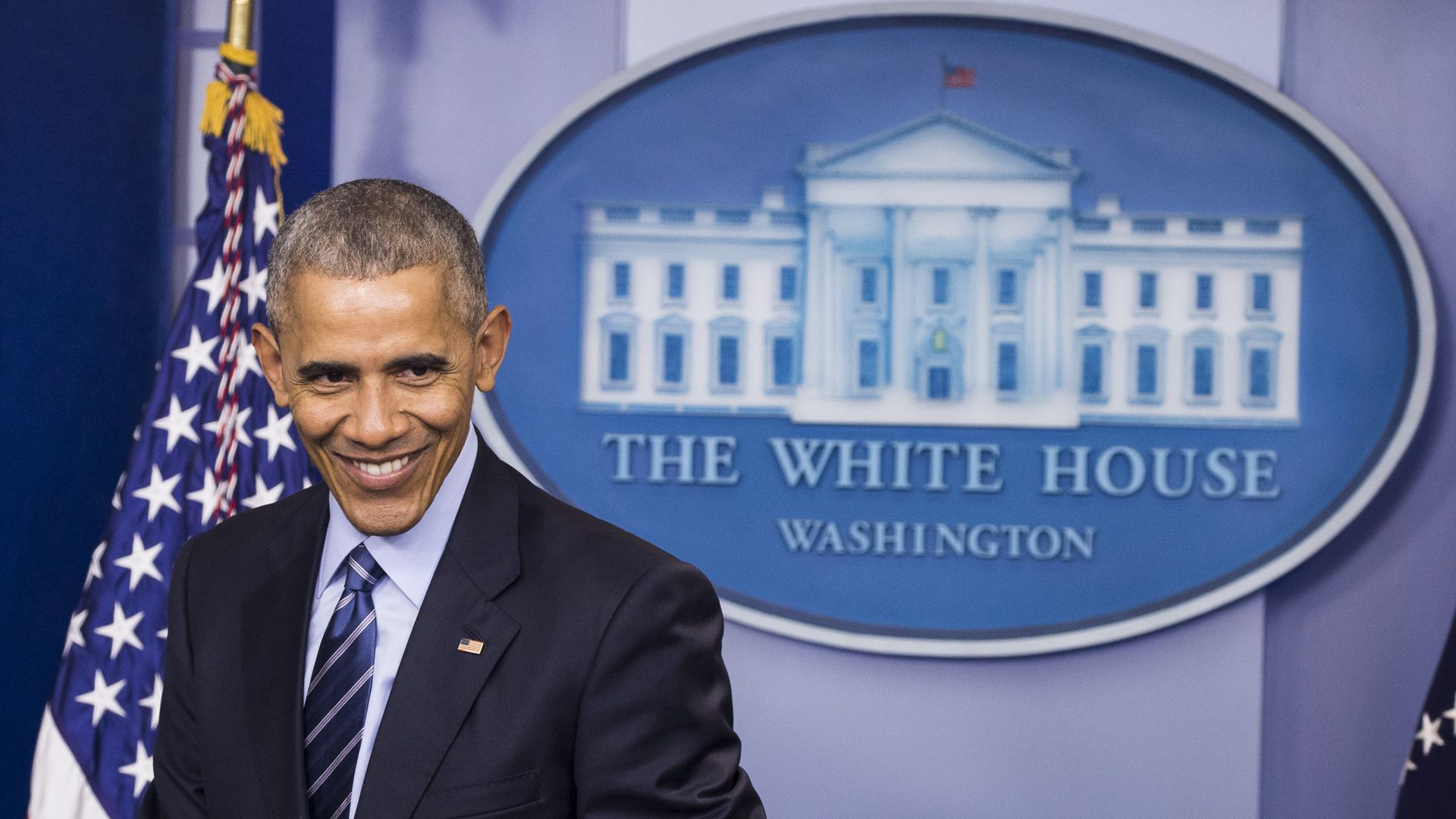 Then-President Obama, smiling, in the White House briefing room.
