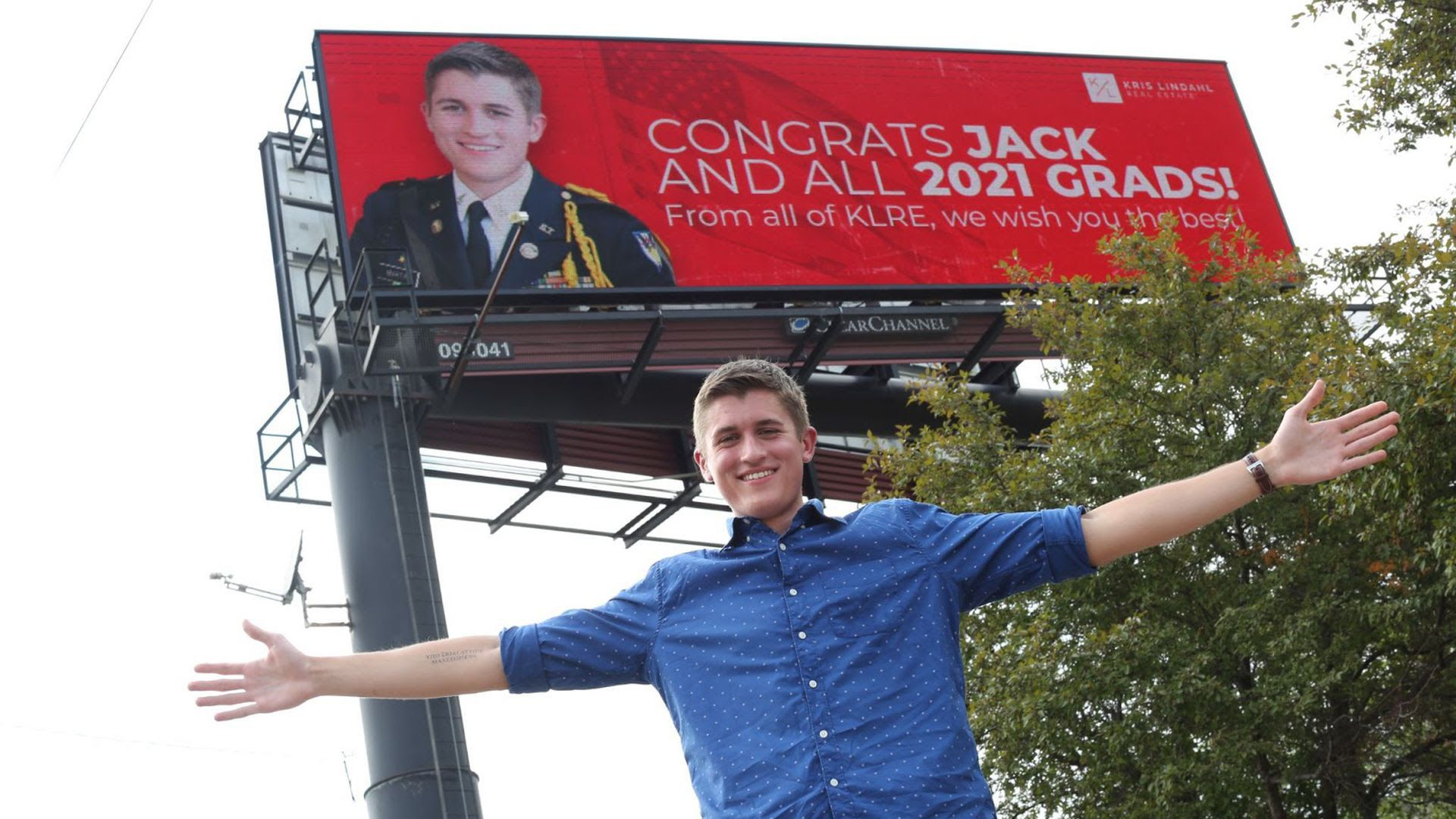 A graduating high school senior stands with his arms outstretched by a billboard celebrating his graduation set up by Kris Lindahl's real estate group.