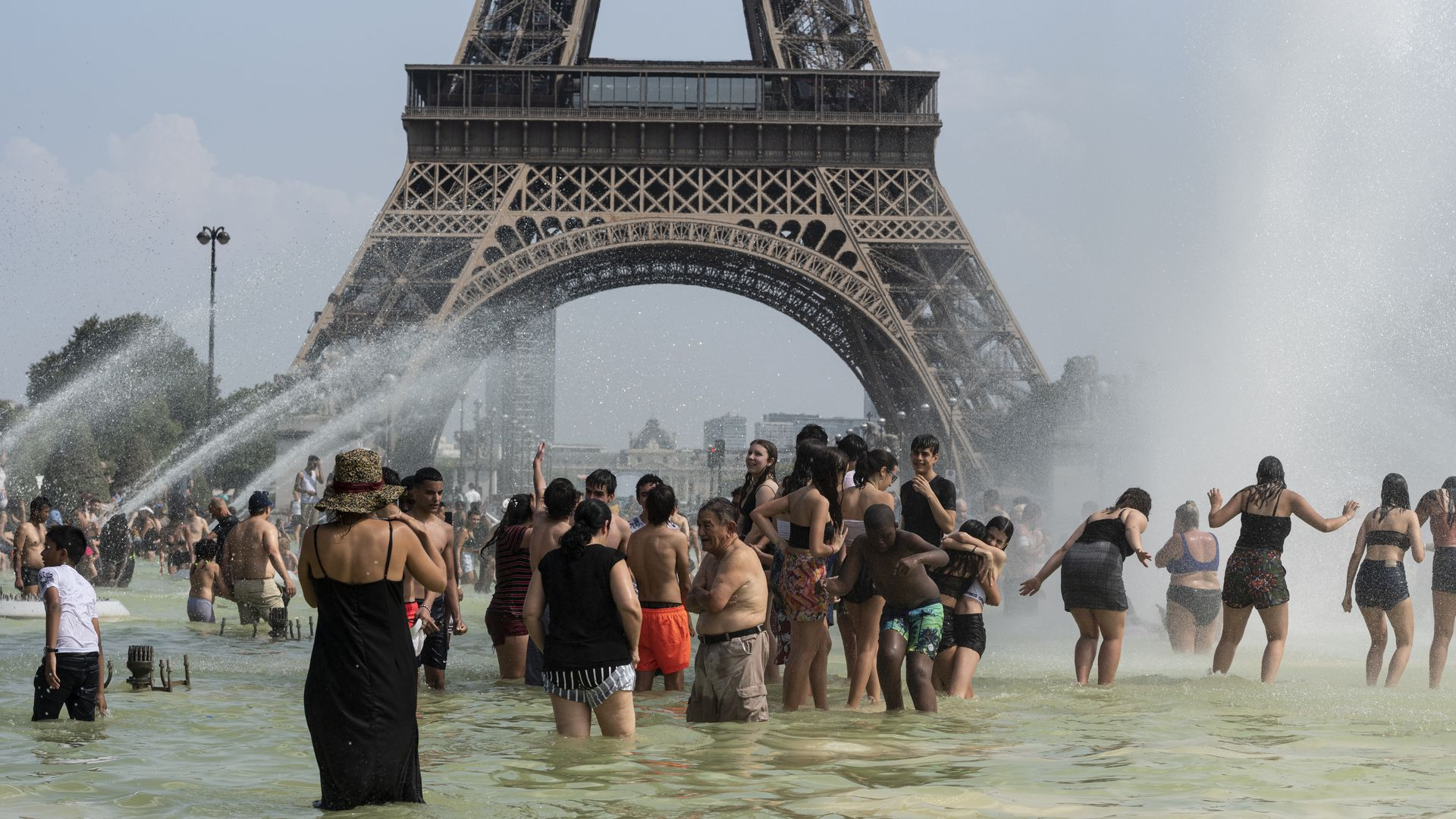 people swimming in water in front of the eiffel tower.