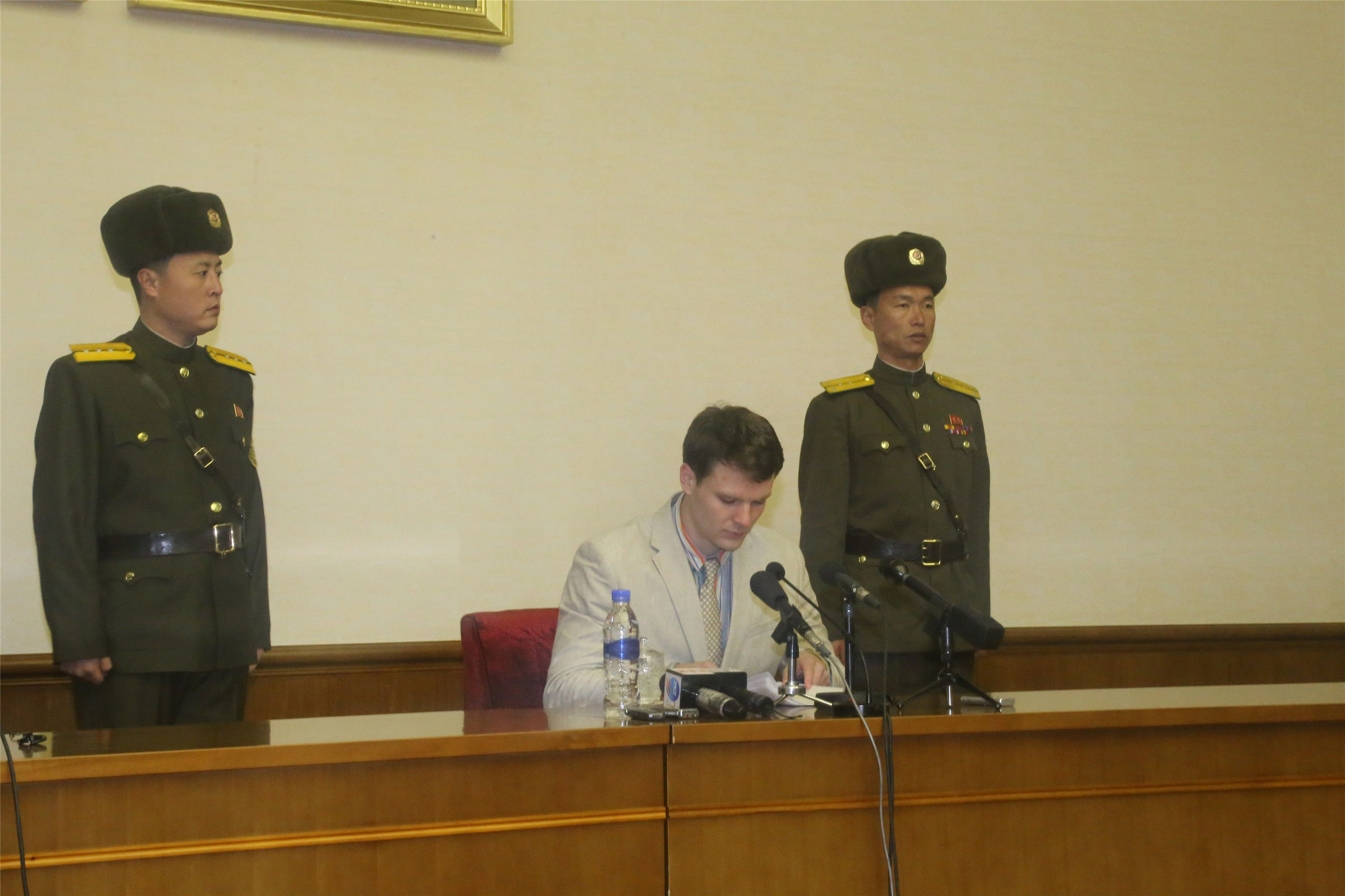 Otto Warmbier is flanked by two North Koreans.