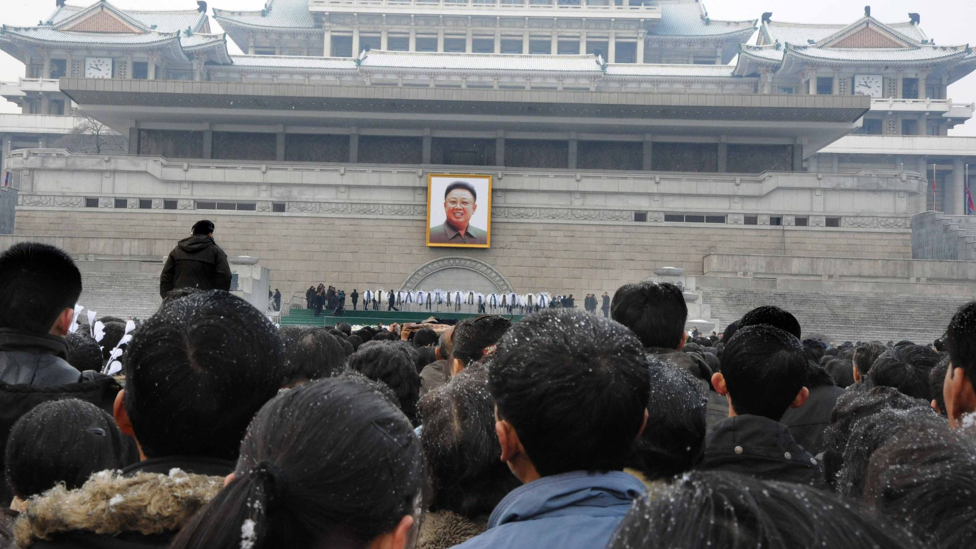 Pyongyang citizens gathering to mourn in front of a portrait of late North Korean leader Kim Jong-il at the Pyongyang Gymnasium.
