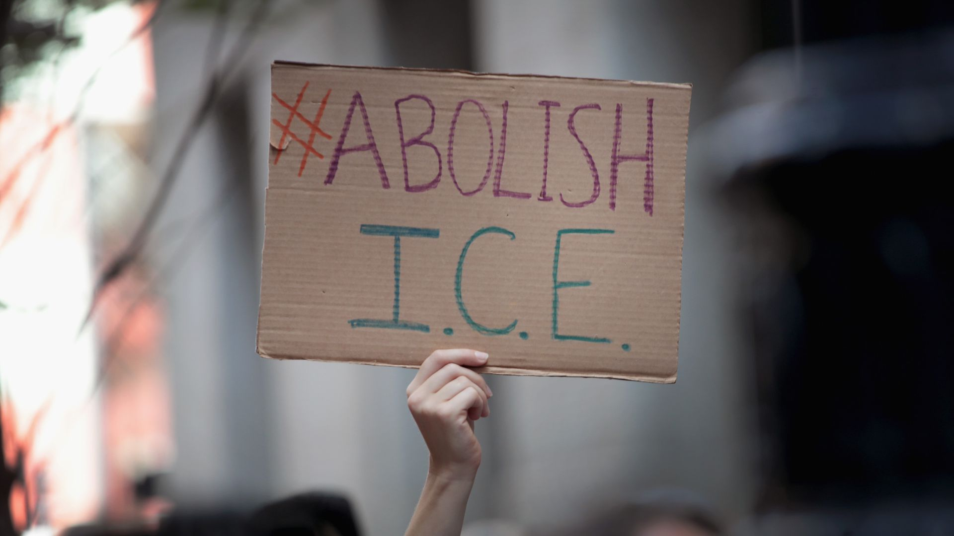 "A hand holding up a cardboard sign that has ""Abolish ICE"" written on it"